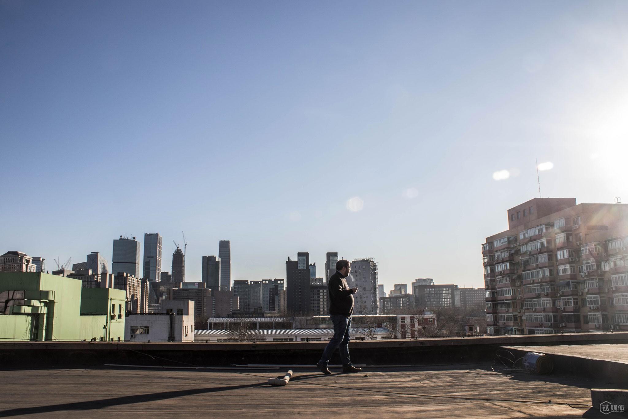 """2016年1月7日,北京三里屯,托马斯·博文在公司楼顶抽烟。托马斯是德国社民党成员,曾是一名议员,他对社会议题一直十分关注,""""中国将出现4亿中产阶级,这个群体很在意生活质量,对食品安全和消费品安全问题非常关注,这是优恪的机会,这样的独立第三方测评服务,在中国是前所未有的。"""""""