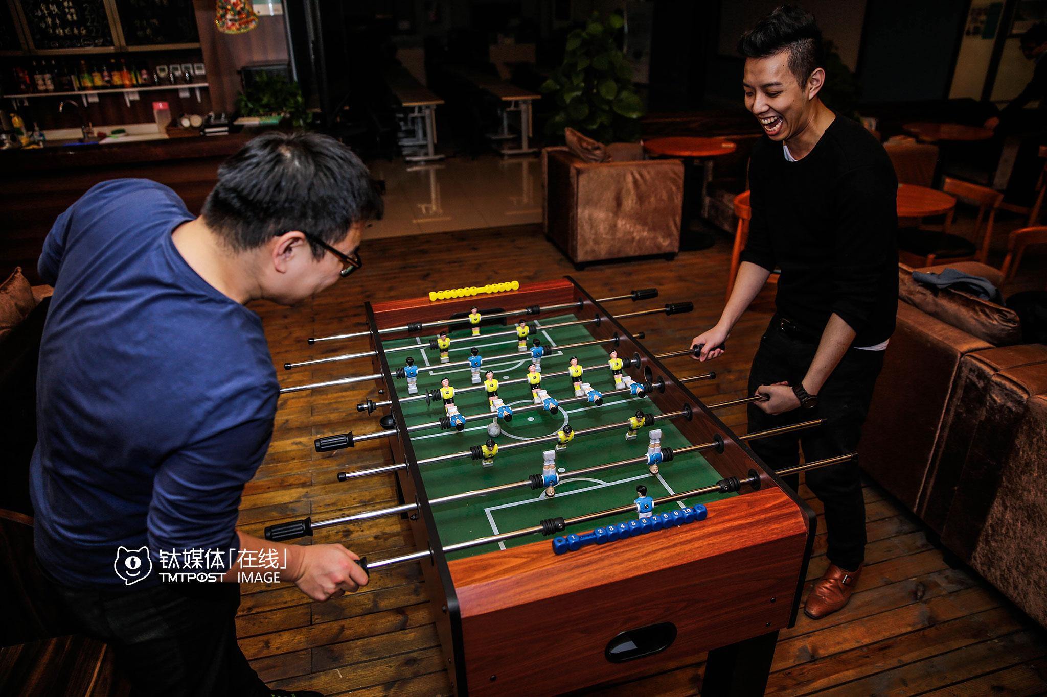 3月4日21:00,石景山创业公社,简少年(右)与合伙人MIke在休息区玩桌面足球。