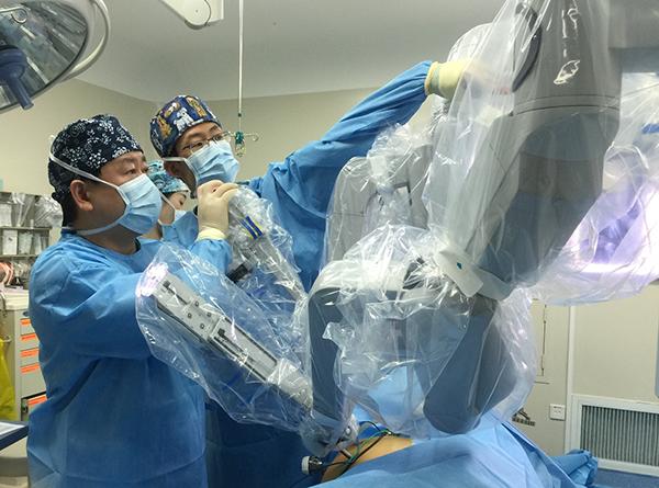 手术开始前,朱刚和同事正在对机械臂进行调整。