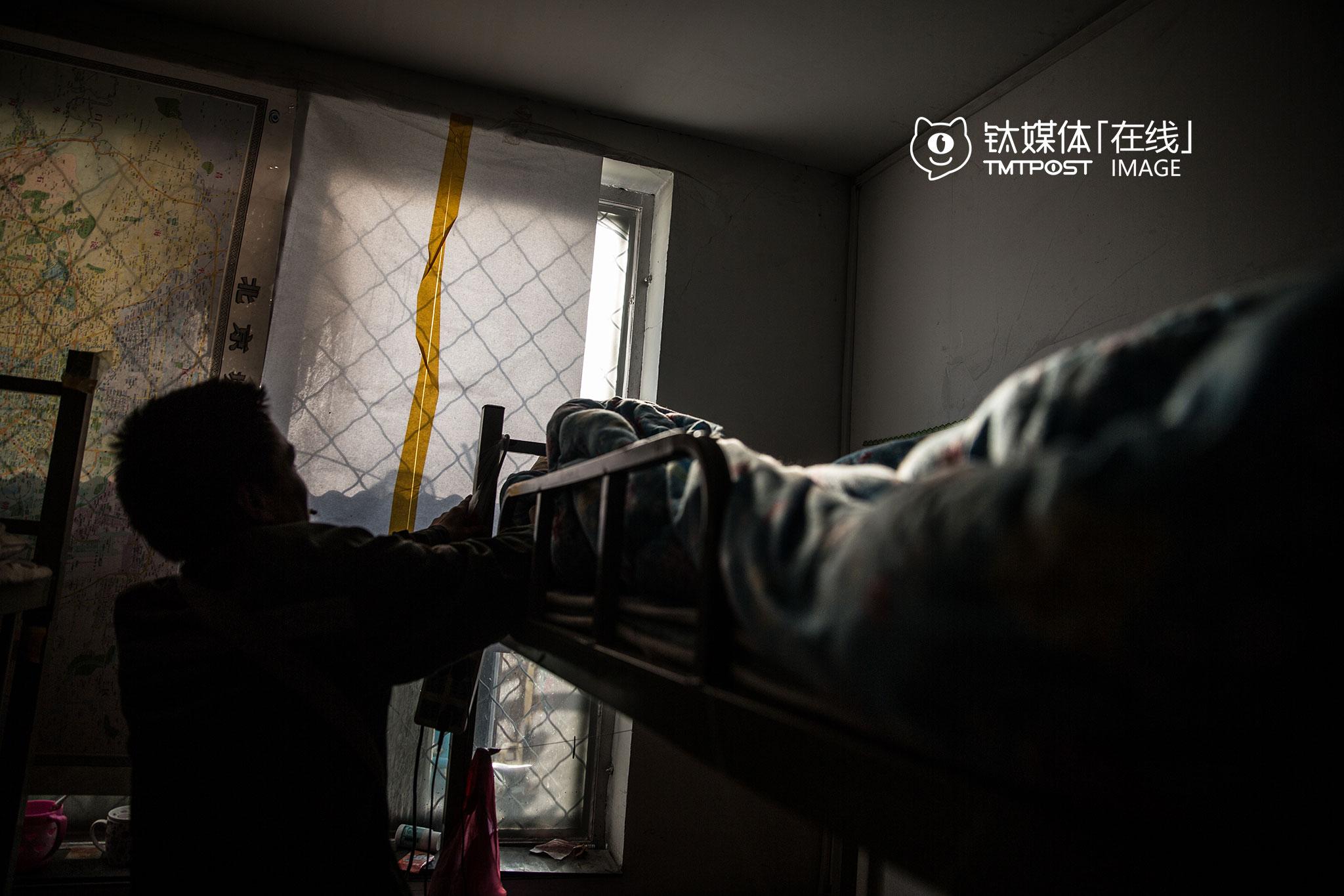 """快递站点包早晚餐和住宿,这张高低床是他休息的地方。路飞读了一年多中专,16岁就出门打工,在建筑工地做过,干过快递,当过水管工。2016年春节后,他在老家看到北京的招工信息,于是跟着中介到了北京,""""一群人,被送到北海公园附近一个地下室,中介要我们签合同跟他们干活,一千五一个月,我不签,他们扣了我的手机和身份证,管我要了八百块钱,我才跑出来。""""路飞跑出来后,上了一辆出租车,要司机把他送到北京租房便宜的地方,司机一直开到朝阳区双树,他下车找了个地方落脚,才找到这家快递公司上班。"""