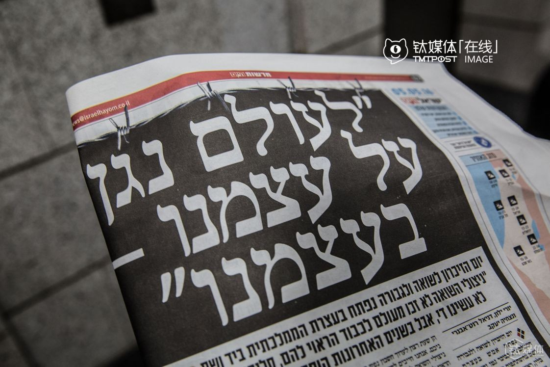 "It was May, 5th, 2016, Israel's Holocaust Remembrance Memorial Day. A piece of local newspaper at Tel Aviv issued a special feature to remind readers of the tragedy. In the above picture, the Hebrew title means ""We shouldn't be slaughtered again"". At 10:00 AM, Sirens sounded across Israel Monday to mark a moment of silence to honor the memory of the victims of the Holocaust. The two-minute siren at 10 AM is an annual tradition in observance of Holocaust Remembrance Day. The traffic stopped, and people would get out of their cars and put away their work, paused and lowered their heads in remembrance of the 6 million Jews killed by the Nazis during World War Two."