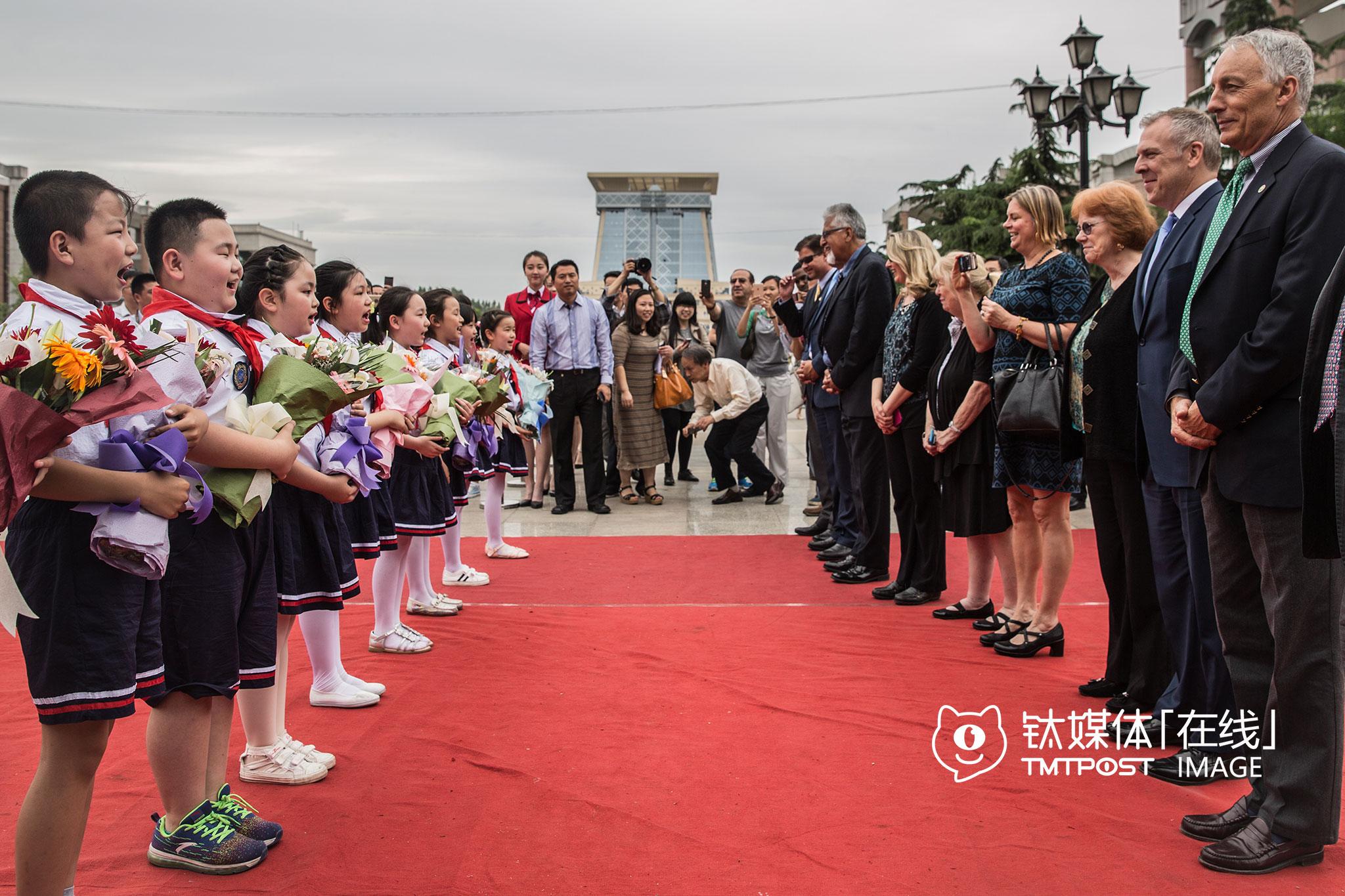 """郑州,西亚斯国际学院为硅谷市长团举行的欢迎仪式上,在齐声喊出""""Welcome to Zhengzhou""""后,小朋友列队向市长们献花。"""