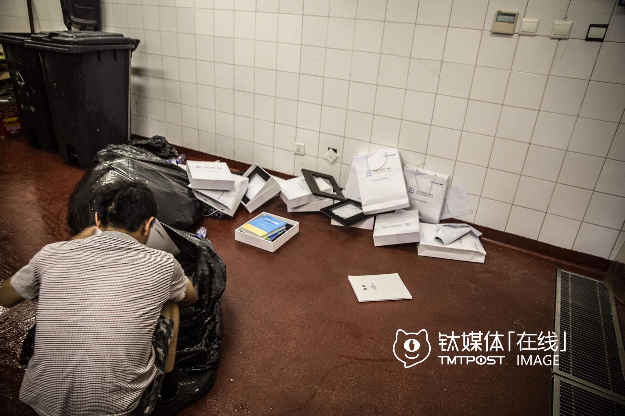 """北京,国贸三期B2的垃圾房,一个会议结束后,保洁从现场收来了与会者留下的大量纸袋、礼物,""""里面有书,但我也看不懂,没用,待会就有回收废品的来拉""""。"""
