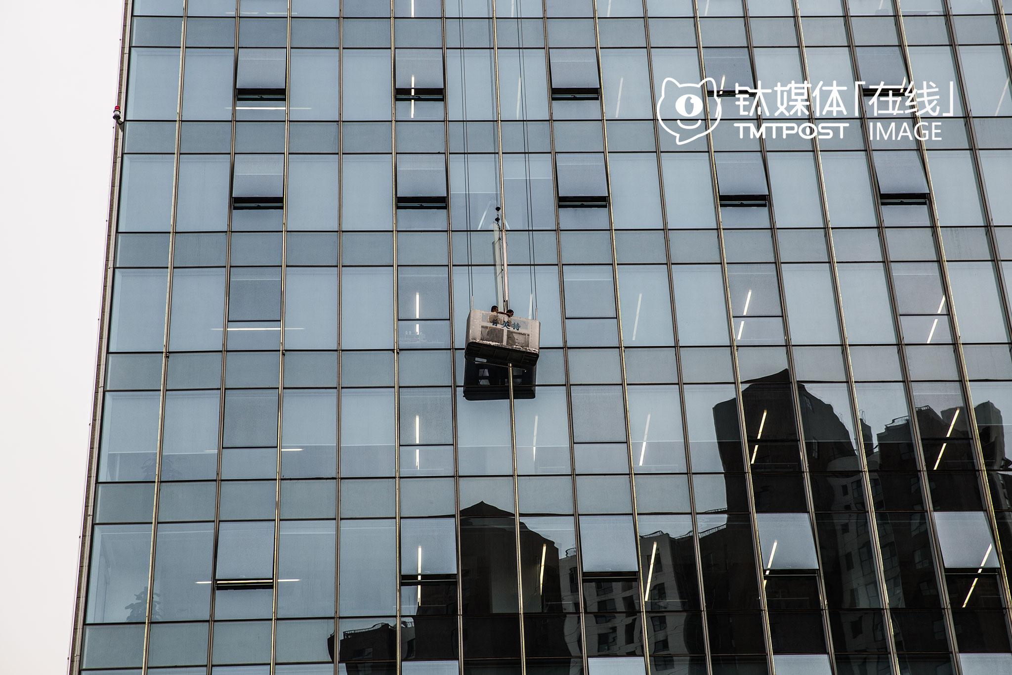 2016年7月14日,望京绿地中心,阿里巴巴北京总部,两名工人在进行玻璃幕墙清洁。这是阿里在杭州以外的地方所购置的第一栋办公楼,悬挂在150米高空的阿里标志,正在成为望京的新地标。而此时,距离马云第一次带着团队到北京寻找机会,已经过去19年。