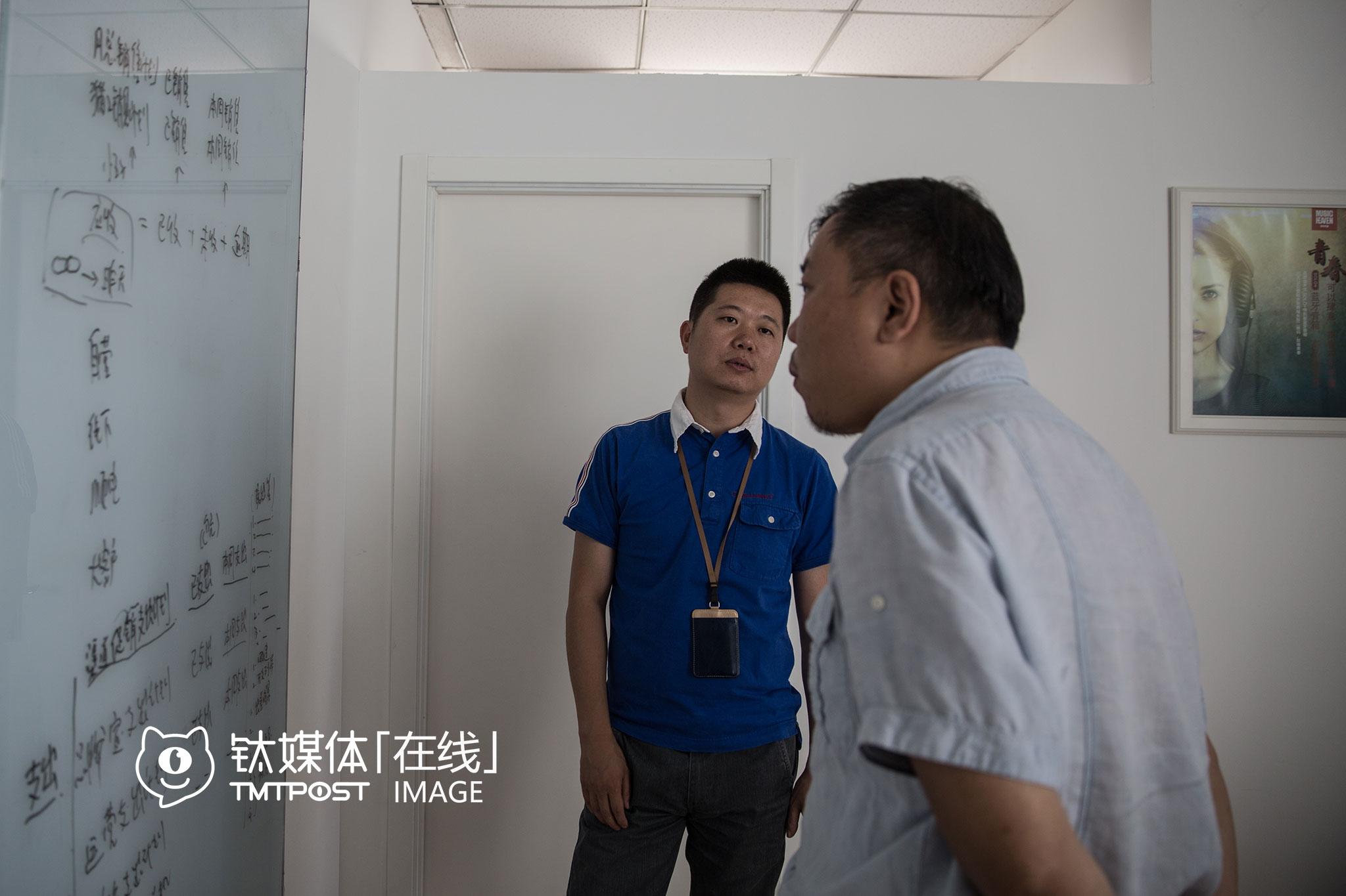 """2016年7月14日,方恒国际中心,云动创想办公室,联合创始人戴明志(左)和同事在商讨工作,由于业务扩展,这家公司刚刚从方恒国际的另一套小办公室搬到这里,""""望京很完整,工作、生活、孩子读书,不出望京都能解决,这里在北京东北角,平时到国贸CBD、中关村开会也还比较方便,望京里面不堵车,但唯一不好的地方就是进出望京太堵了,浪费时间,所以如果谁想来望京创业,最好把家安到望京来,节约时间。"""""""