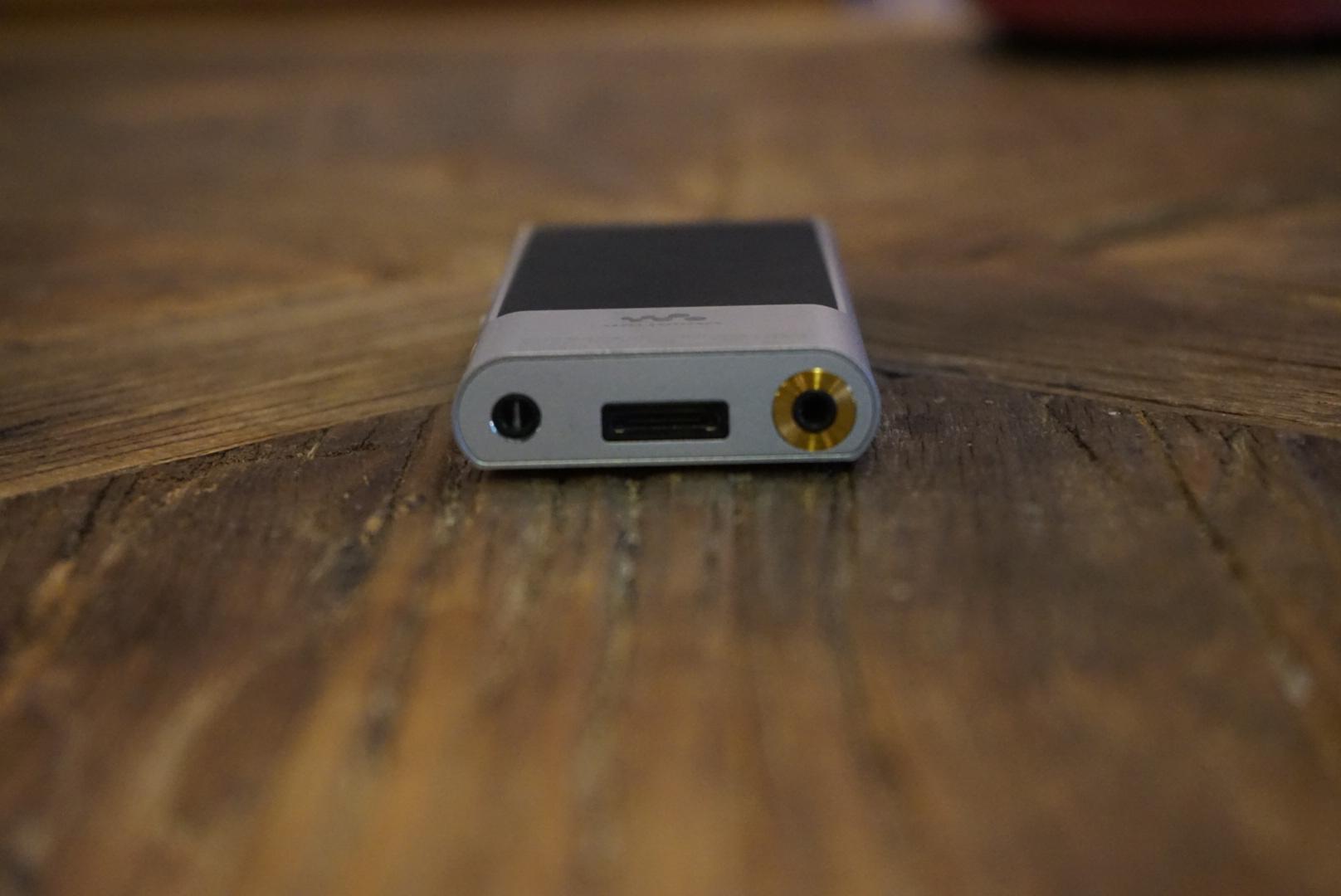 背部依然是该系列典型的翘屁股设计,整体采用了一种磨砂材质,防滑性极佳,另外NFC的标签同样也在这里。耳机插口也是这些年来SONY播放器风格,ZX系列惯有的3.5mm镀金耳机口成为了标配,正面按键上贴着一枚明显的 Hi-Res 小金标,这可以索粉们为之疯狂的最重要原因,具体我们后面再讲。