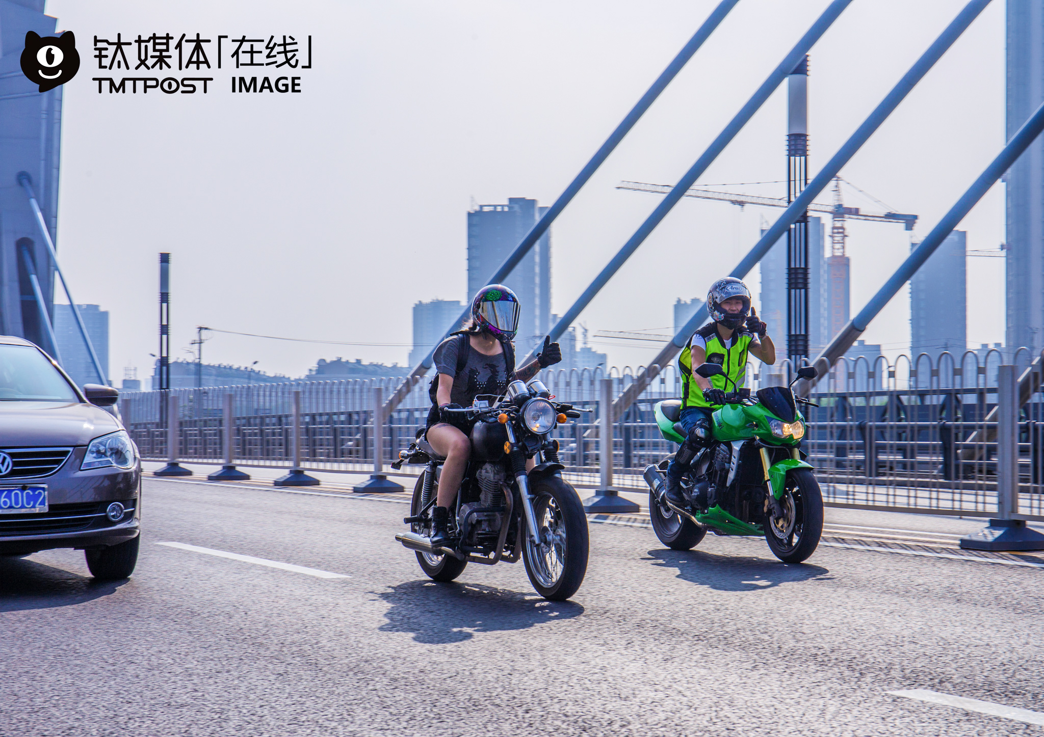 "Bu Yi (the motorcycle rider to the right of the picture) was riding on the Tongzhou north Tunnel Bridge, and showing his greetings to another motorcycle rider he encountered on the road. ""If other motorcycle riders found that I didn't wear protective clothing or ride on the wrong road, they would approach and barge me,"" he explained. For him, strict intendance among motorcycle riders will not only improve our safety awareness, but also improve the riding environment for motorcycle riders, and this is what he referred to as the ""rider spirit"". According to transportation rules in Beijing, riders could ride motorcycles with Beijing-A plate inside Beijing, but they could not ride motorcycles with Beijing-B plate inside the fourth ring."