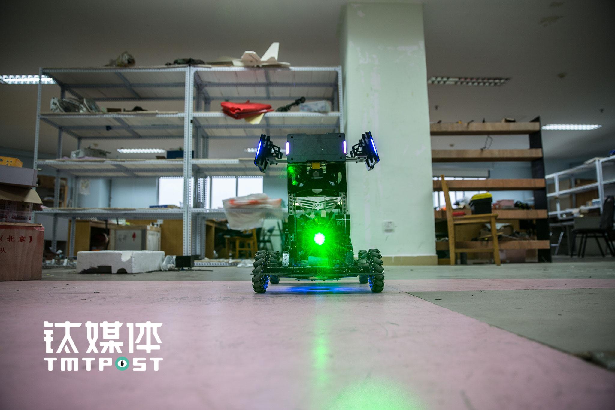"""中国石油大学(北京),SPR机器人战队大本营,一台刚""""英雄""""机器人启动后,瞄准器射出绿色的射线。"""