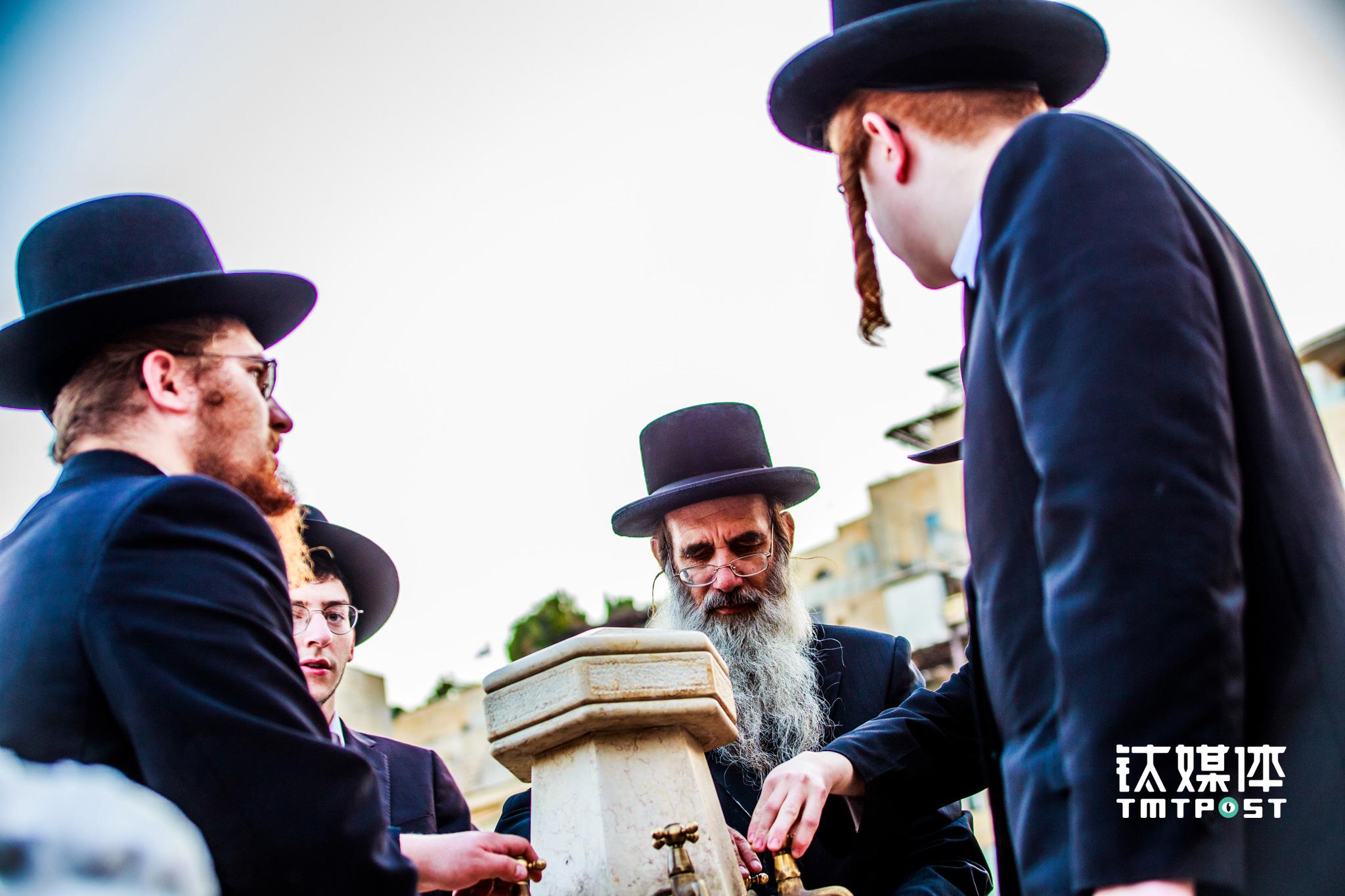 """在耶路撒冷,前来哭墙祷告的犹太教拉比。以色列政府供养了约50万个犹太拉比,专职从事严肃的宗教事业,毕生钻研于犹太教的智慧与知识,并鼓励他们结婚生育。作为犹太民族的精神支柱,这些拉比以传教作为终生事业,成为犹太教里的""""智者"""",熟知犹太教典籍,解答犹太人的宗教和生活问题。(图/朱玲玉)"""