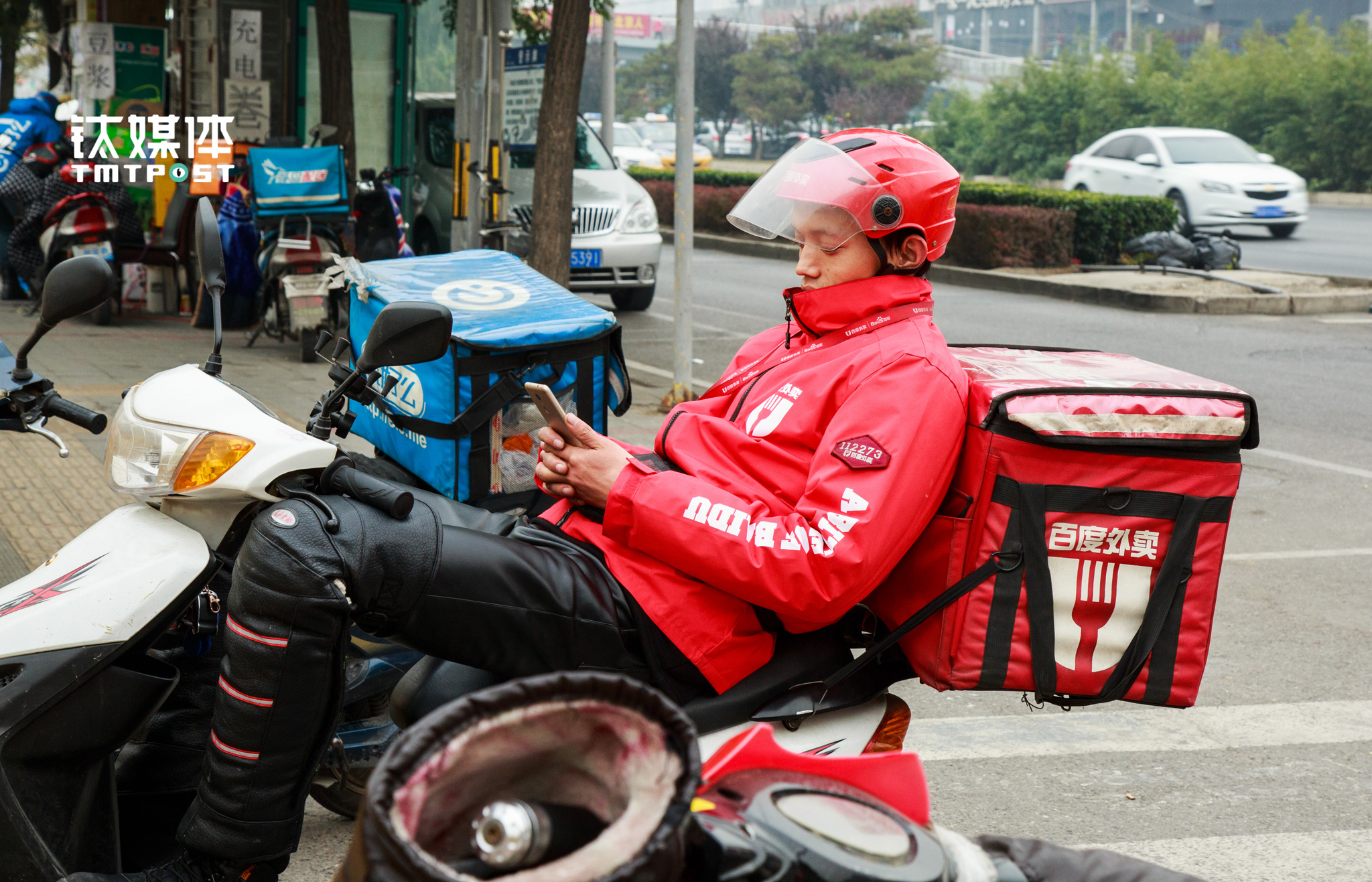 After the peak hours at 2 pm, a deliver who just had some lunch was somehow napping while holding his smartphone. The regular working time for the delivery guys is from 9 am to 10 pm, while the night shift could last until 3 am.