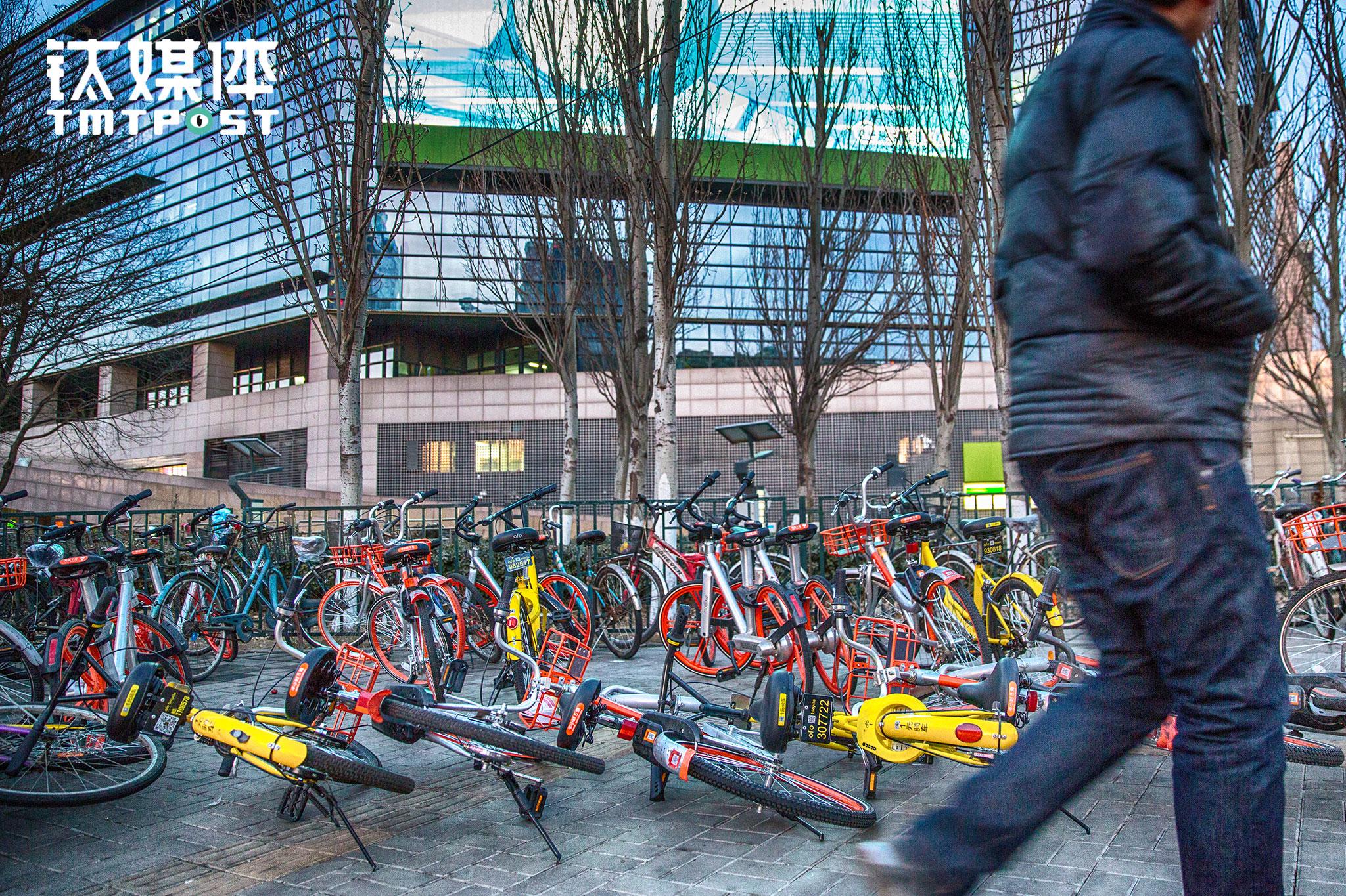 2017年2月22日,北京东直门,行人从一排倒掉的共享单车前匆匆走过。据第三方报告,截至2016年底,中国共享单车市场整体用户数量已达到1886万,预计2017年年底将达5000万。截止2017年2月,出现在北京的共享单车总数达20万辆。