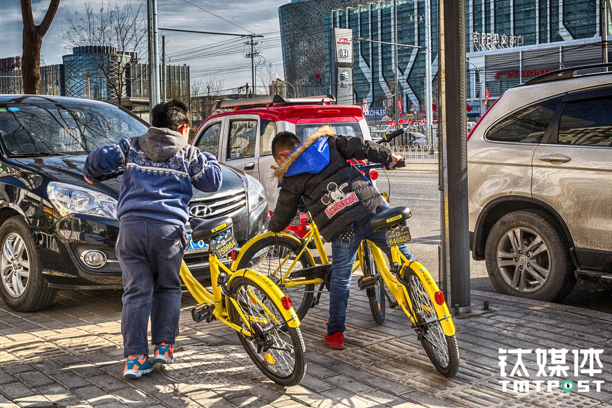 """朝阳路,两个小学生尝试打开一辆停在路边ofo的锁,""""有时候车锁一按就开了,有时候根本就没锁"""",俩人说,时不时能找可以打开锁的ofo,再骑着""""逛一逛""""。根据《道路安全管理条例》,未满十二岁的儿童被禁止在道路上骑自行车。虽然共享单车APP对未满12周岁的注册者进行了限制,但仅此一条似乎难以阻止类似情况的出现,而其背后则是难以忽视的安全问题。"""