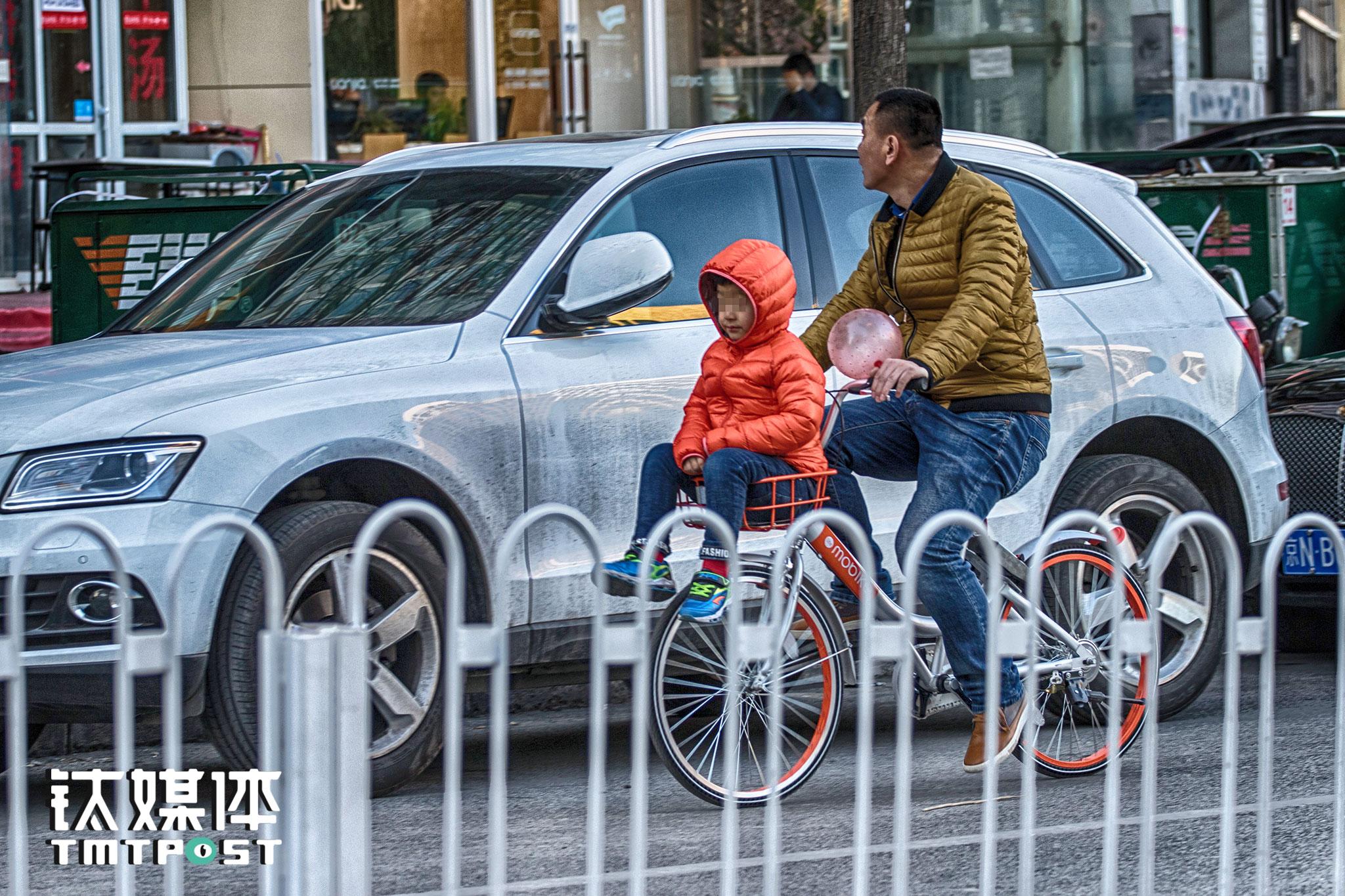 国美餐饮街,一名成年男子在骑行中让孩子坐在摩拜单车的车篮里。