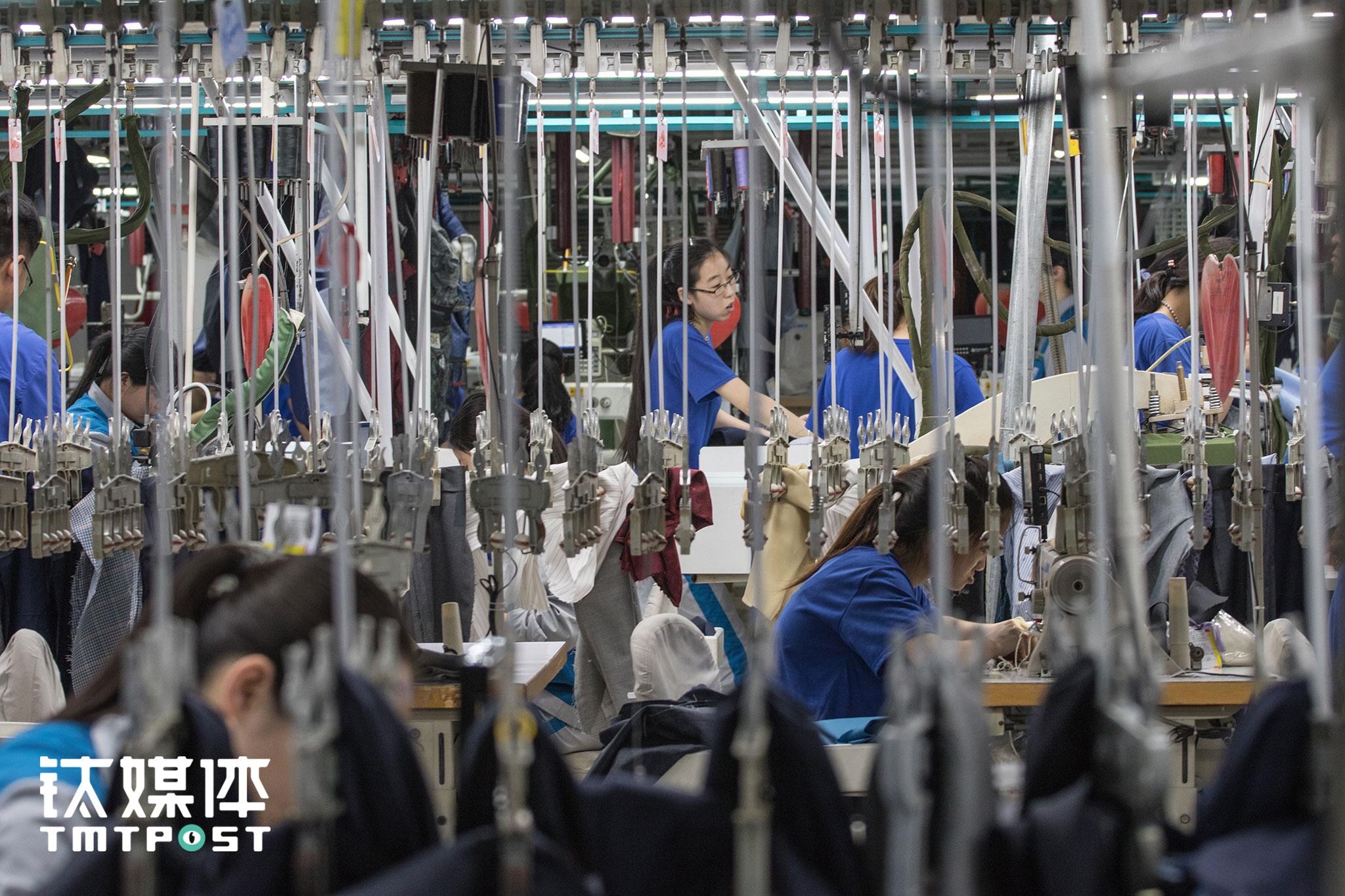 在酷特智能的生产车间,每件西服从布料开始,就通过吊挂系统在不同工序组别和岗位之间传递。