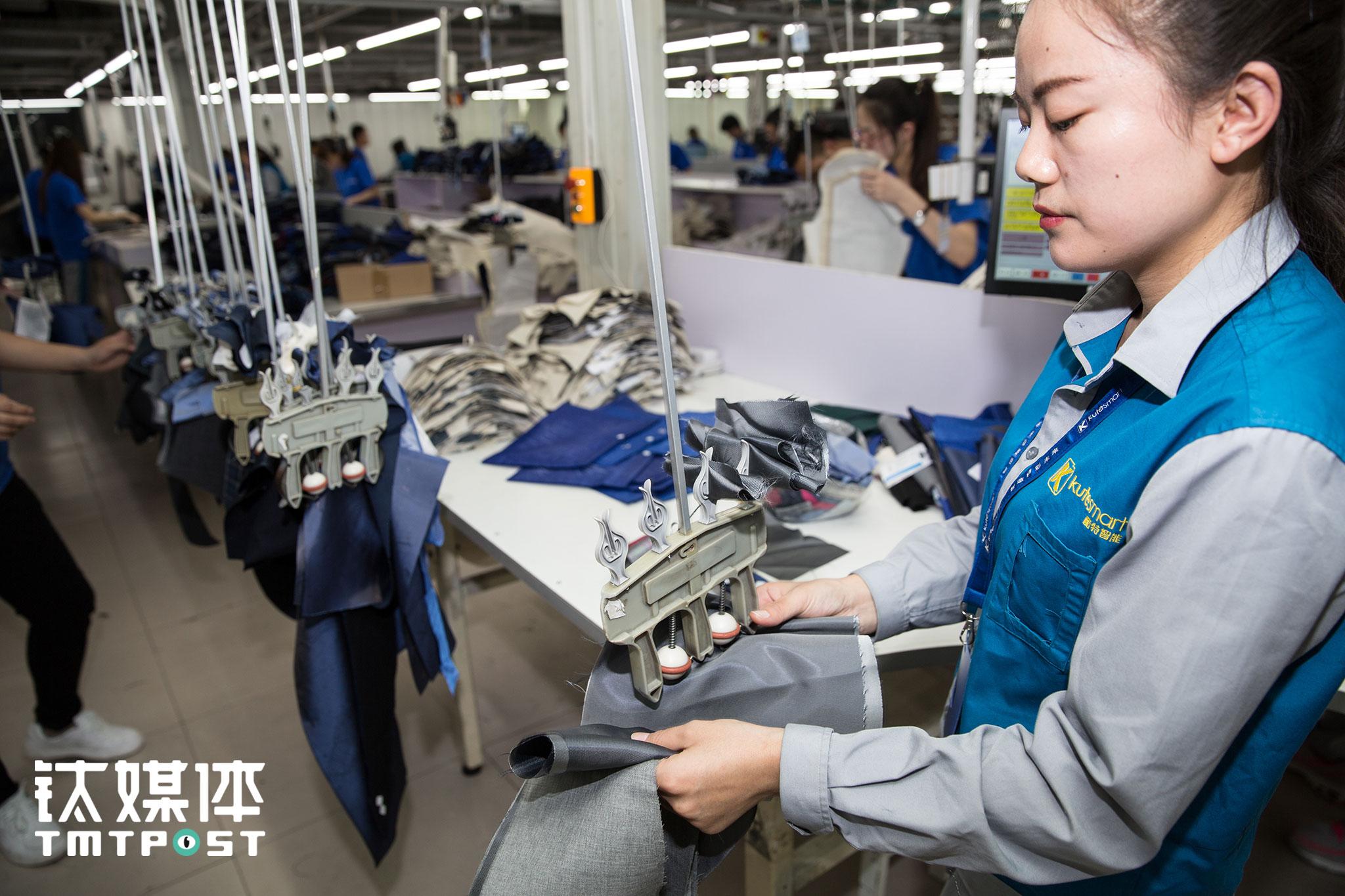 一名工人将裁剪好的布料与电子标签卡一道夹到吊挂上。
