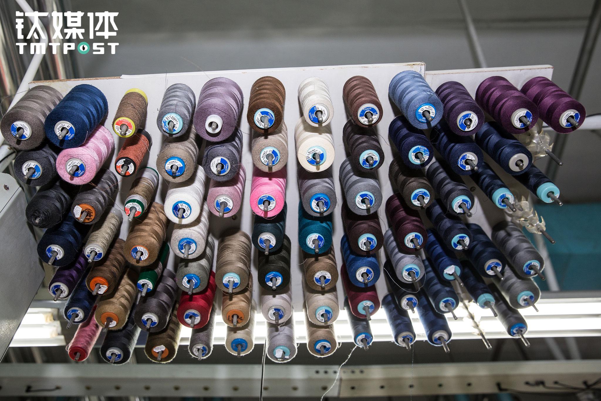 一名熟练的缝制工人,工位旁边和顶部,加起来至少有100种品类、颜色的线捆,由于每一件衣服都不一样,他们需要在这些线之间迅速地切换。