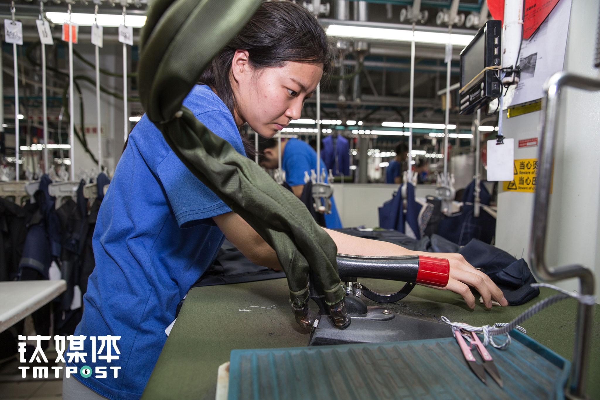 一名女工人在动作娴熟地熨烫西服布块。酷特工厂目前有2000多名工人,90后占相当一部分,千人千面的定制西服,每一件的工序都有所差别,这让他们时刻保持着专注。