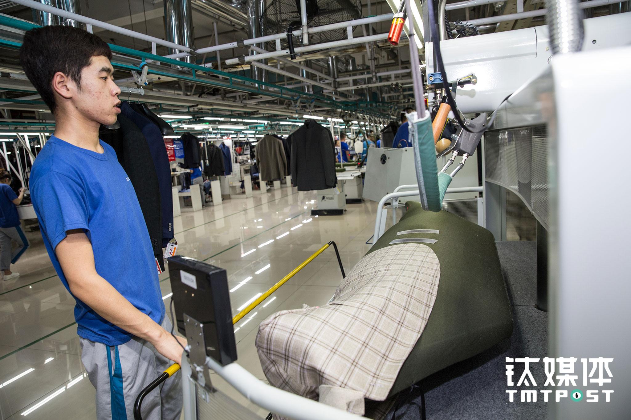 智能整烫线体上,一名工人在为西服做出厂前的熨烫。