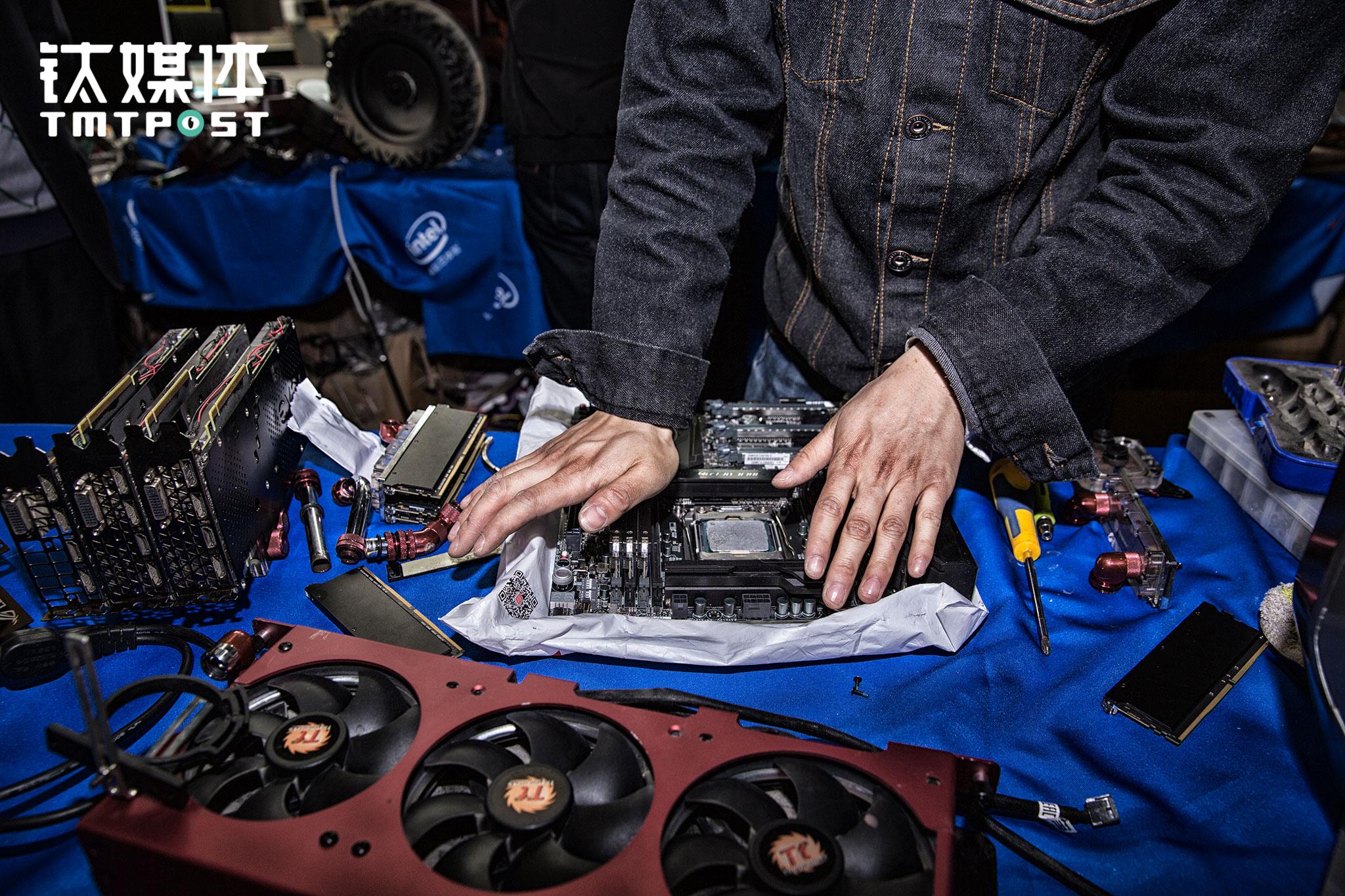 """一名技术员准备测试一款主板。FUXK会为每个作品拍一段短视频,用于赞助商的推广。除了一些IT配件,还有部分零配件比如特殊的螺丝,需要到沿海工厂定制。MOD的改装本来就非常个性化,所以单个定制量不大,有时候为了等工厂排期,需要很长时间。还有一些特殊零件,需要在德国定制,""""但是德国的厂子特别好,一个两个配件也做,有时候要等8、9个月才给做出来,但做工和质量都梅得说,一定很完美""""。"""