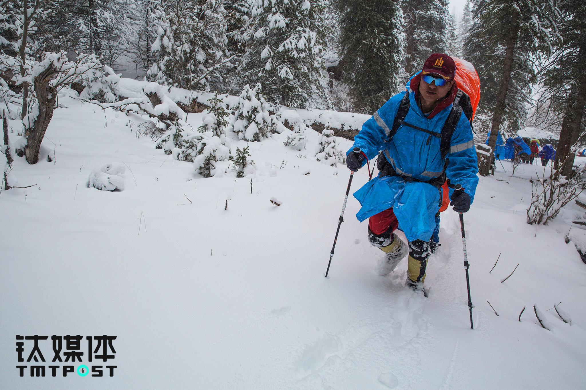 """森林里积雪最深的地方,已经没到大腿根,雪地行走很费体力,领队必须走在队伍最前面趟雪,才能让后面的队员比较轻松地通过。这些线路江湖重复走过多次,对他来讲风景已经不重要了,""""作为领队,我要做的是让每个队员都远离危险并且高高兴兴地走出去"""",即使是同一个地方,每次带不同的队员走,他也会有不同的收获,""""这些收获是我领队生涯中最值得纪念和庆幸的事情。"""""""