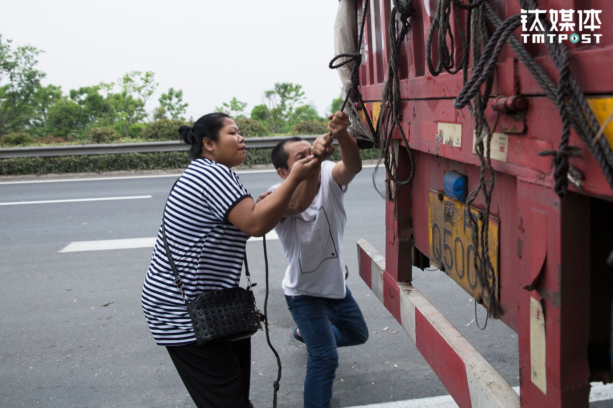 After one day of bumpy journey, the truck load became a bit loosen from the straps. Jin Qiang stopped the truck and tightened the securing ropes at the roadside.