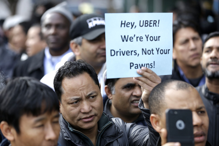 "Uber司机上街抗议,手握标语""Uber,我们是你的司机,不是你的卒子""。图片来源AP/Seth Wenig"