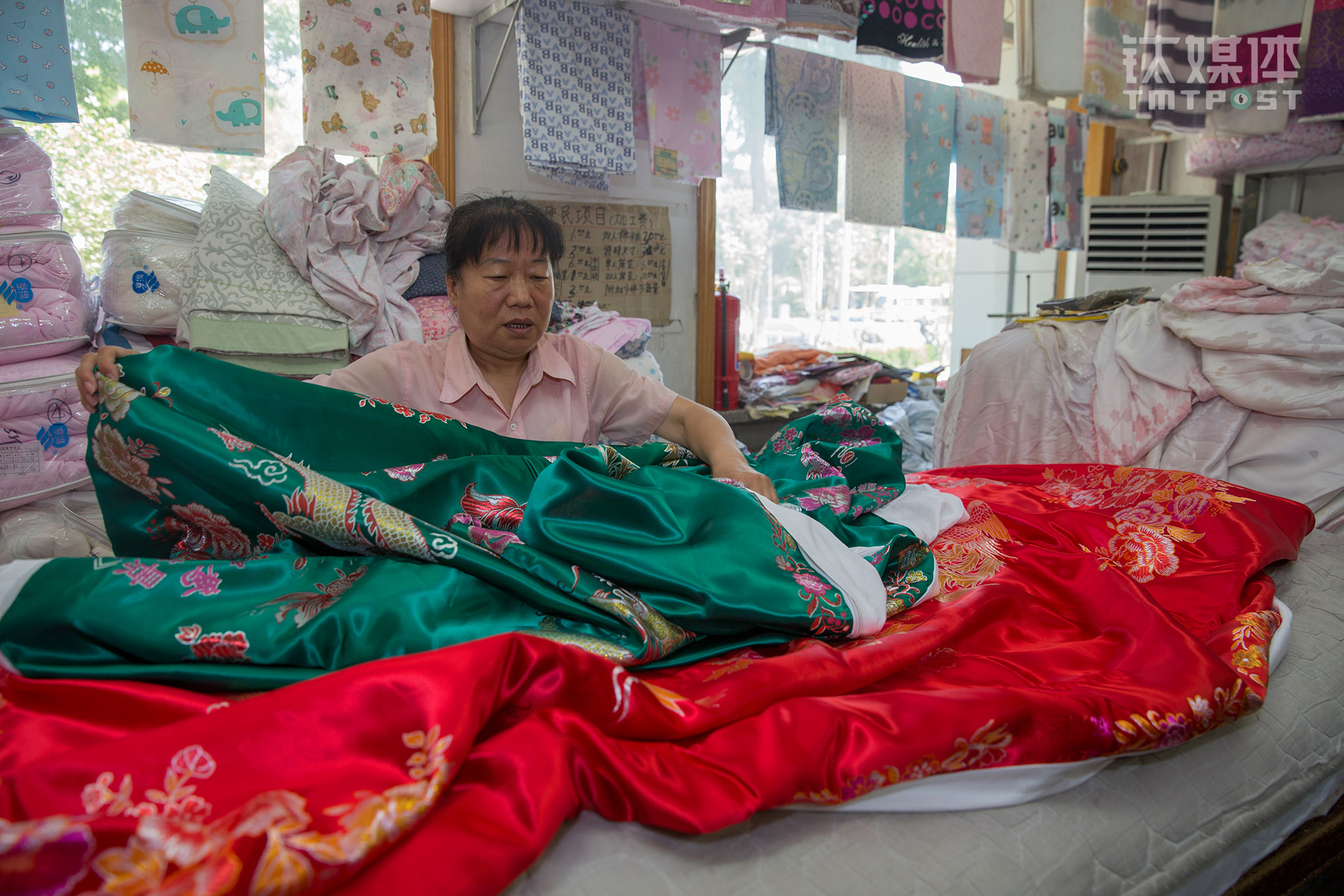"On June 20th, 2017, Liu Huirong from Dafang's fabric section was sorting out some blanket sheets for the customer. The sheets were for a wedding. ""The red one is for the groom and the green one is for the bride. They have patterns of the dragon, phoenix, and peony on them. Usually, people buy a pair. You know, the old generation likes it."""