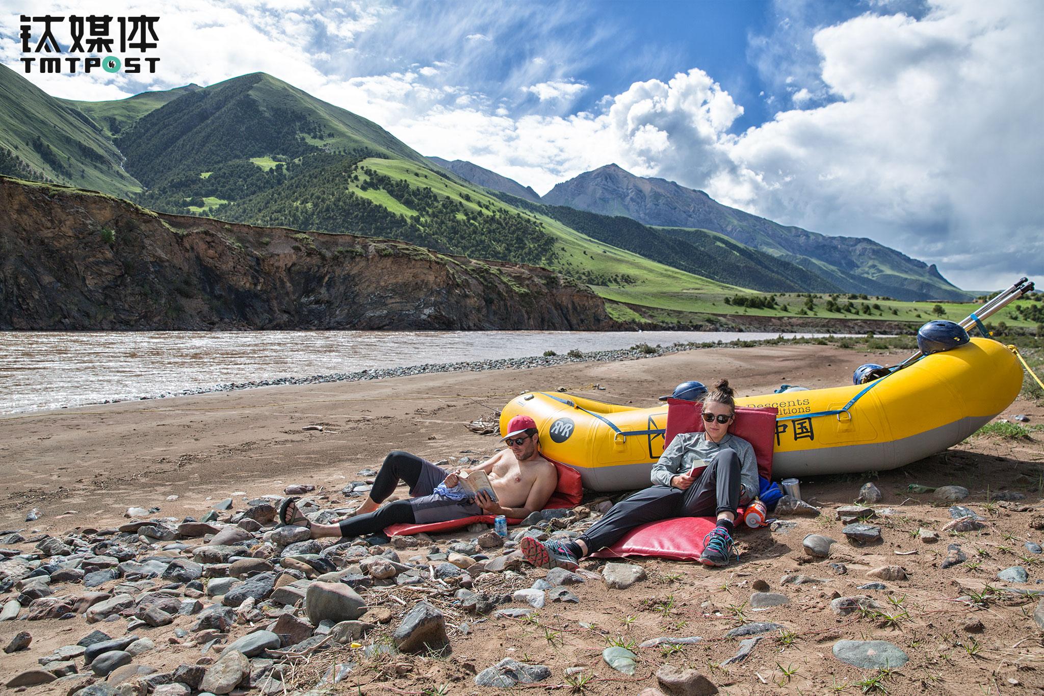 """营地附近,两名客人靠在船上看书。漂流中国设立了""""河流图书馆"""",为客人们提供关于自然、环境和河流的相关中英文书籍。"""