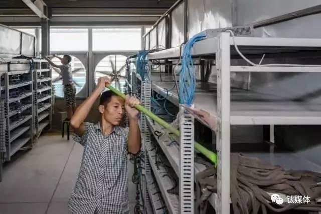 比特大陆矿池的一位清洁员正在用拖把清洁放置机器的架子