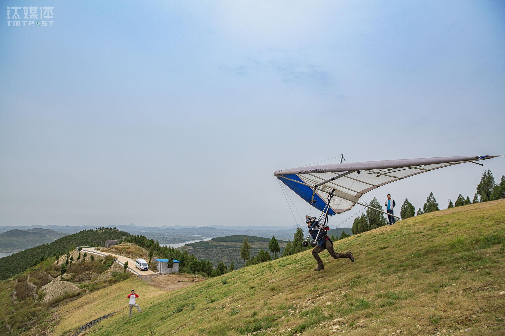 风向气流适合的时机到来,早已组装好三角翼的飞手从山坡助跑起飞。
