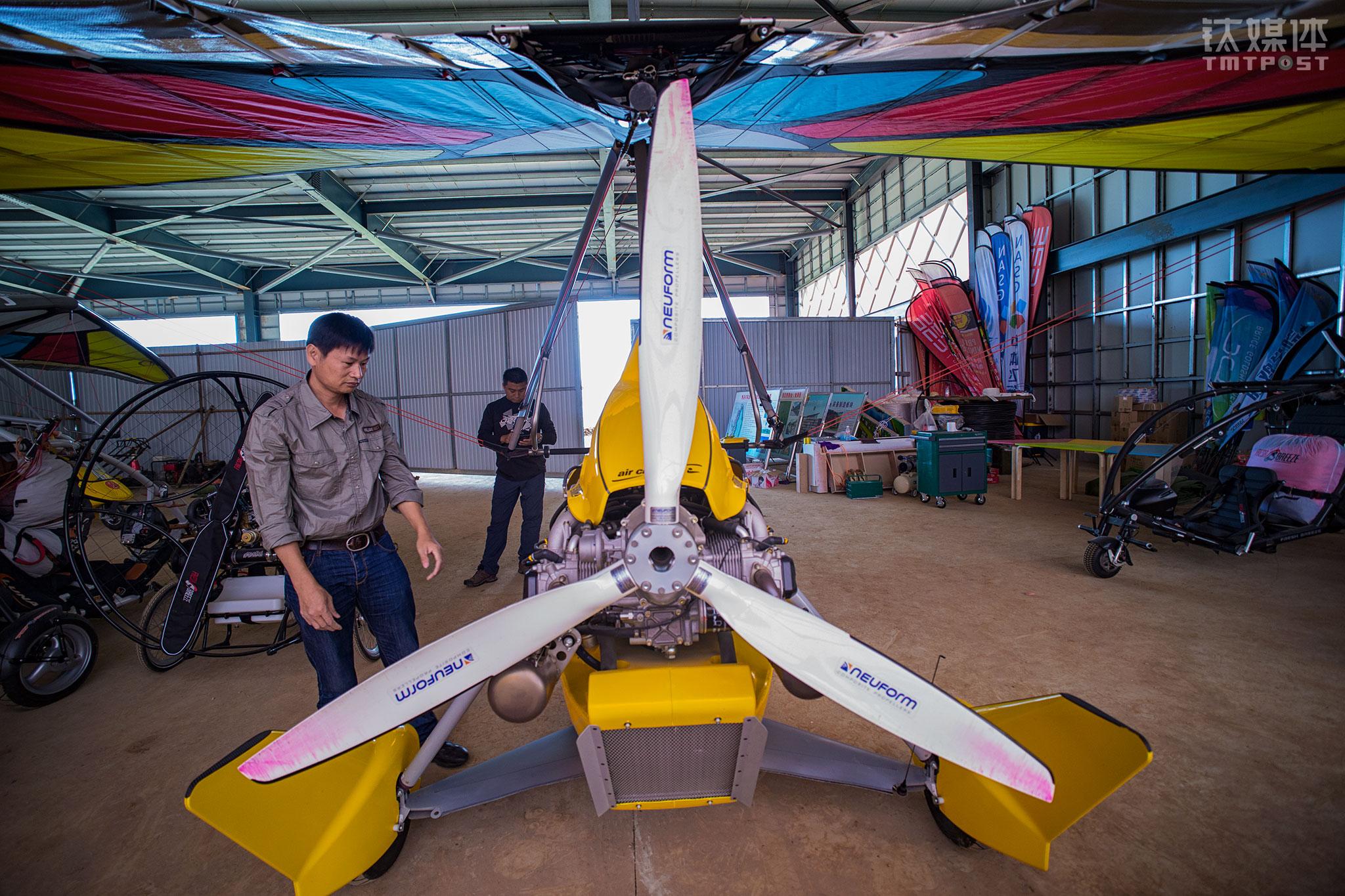 """中体飞行机师彭建平在对机库内的动力三角翼进行检查。彭建平曾是飞机制造厂的机师,在飞行行业从业20多年。这是一个痴迷发动机的人,作为营地机师,他主要工作是对飞行器进行维护,""""主要是发动机,按照发动机厂给的维护时间表严格进行维护"""",彭建平告诉钛媒体《在线》,飞行前后他都要对飞行器的细节进行监控,进行隐患排查。"""