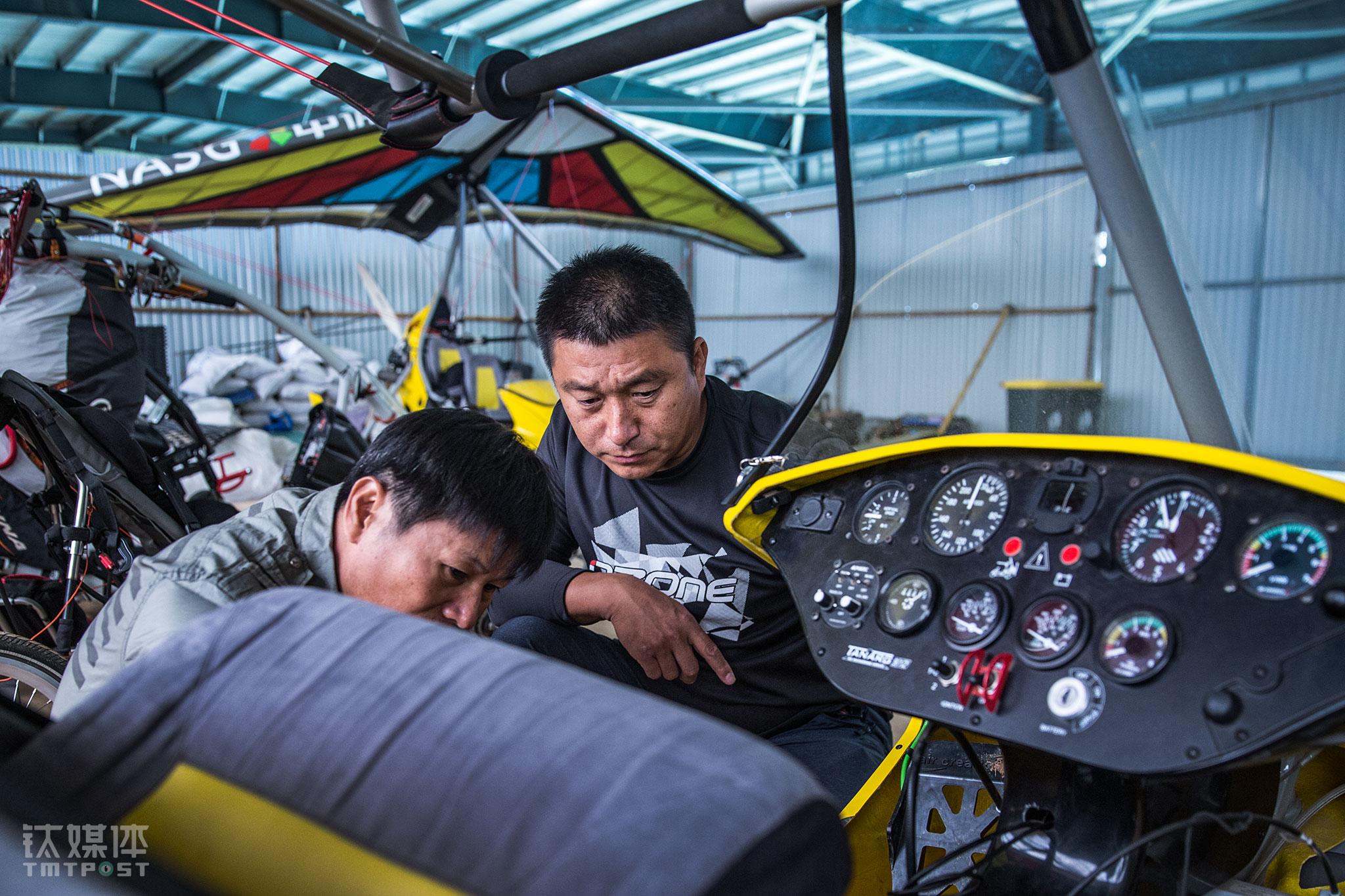 """中体飞行教练范小伟(右)在察看一台动力三角翼的刹车。范小伟是一名""""老资格""""航空人,他从业30多年,曾参与多项飞行相关国家标准的起草和制定和各类国家级飞行比赛标准的指定。""""航空运动和冒险、刺激的关系不大,它需要详尽细致的计划,是一种厚积薄发,而不是头脑发热去冒险"""",范小伟看到这么多年国内这一运动的发展,""""国内刚刚开始走向秩序和规范,在建立良性发展的系统。航空运动这个市场一旦爆发,如果我们的准备和积累应付不了,就会引起很多问题。"""""""