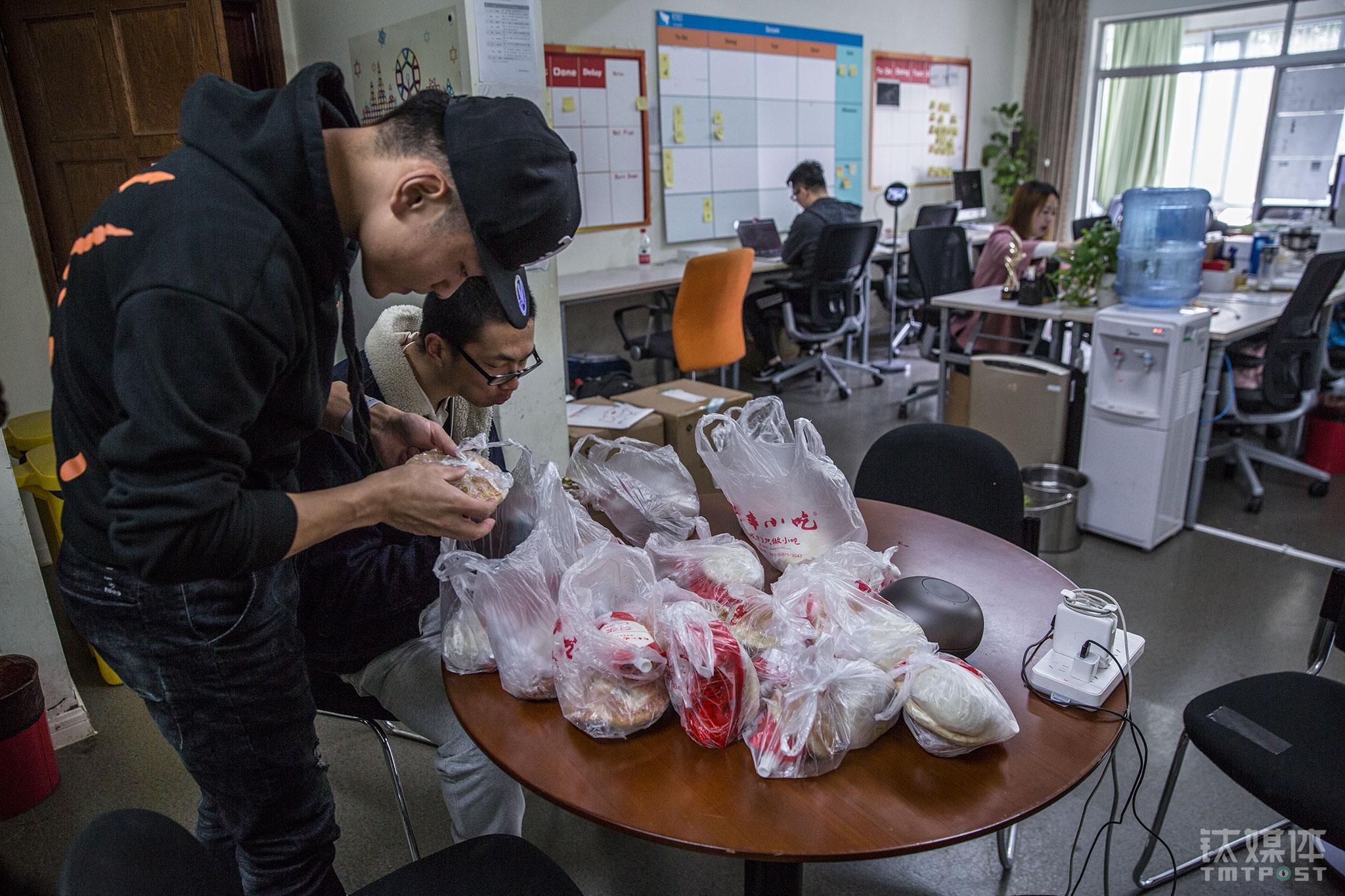 """2017年11月6日9:39,杭州湖畔花园,钉钉硬件团队两名员工拿起公司准备好的早餐。目前这套公寓有钉钉智能前台(简称""""M2"""")和钉钉能通讯中心(简称""""C1"""")两个项目组。"""