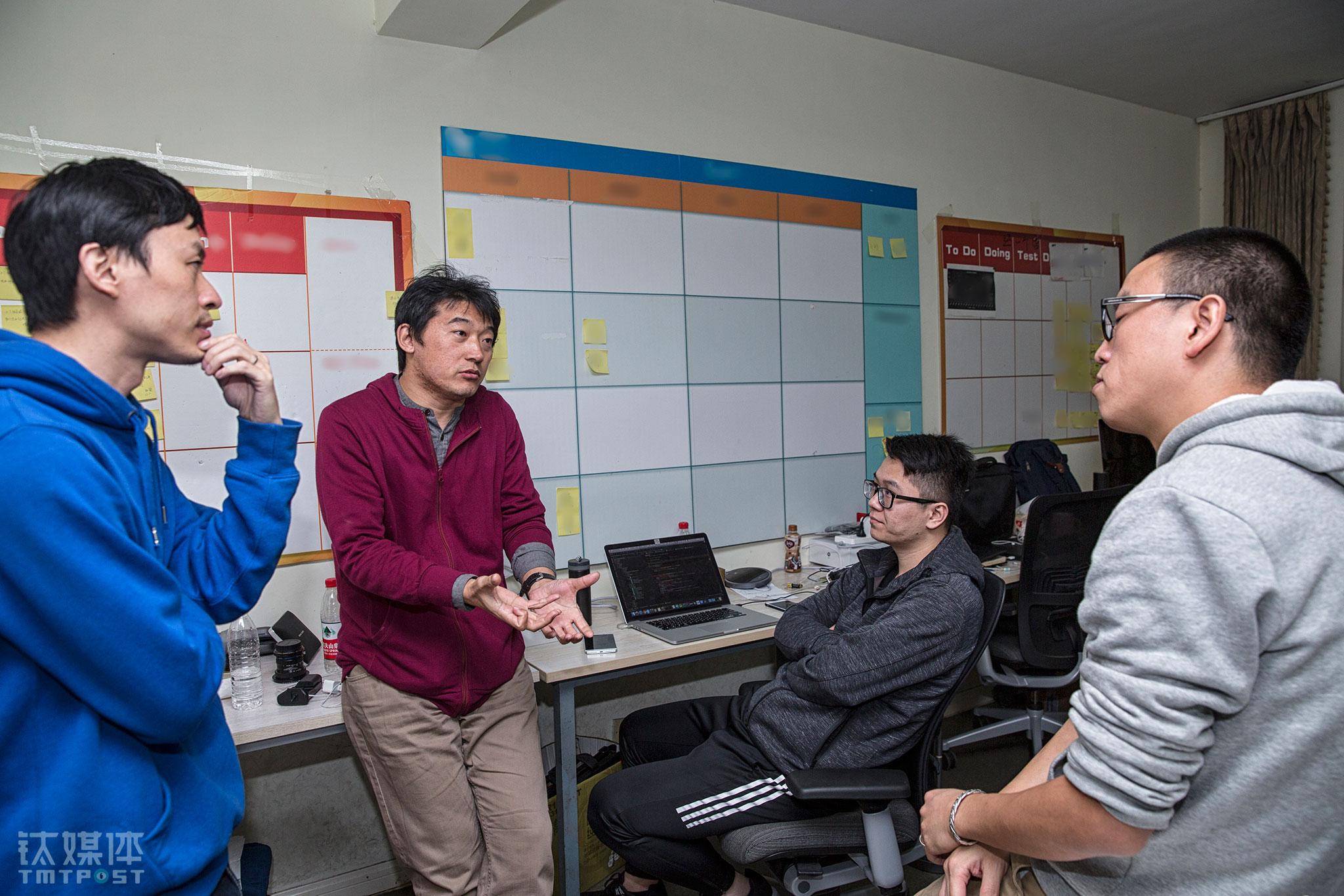 晚上11点半,服务端开发子商(左二)下班回家,在路上碰到的博葵和海俊,三人凑到一起,又聊到了钉钉智能前台更多的可能性,于是索性一起折返办公室,找到开发的同事龙翼讨论了起来。