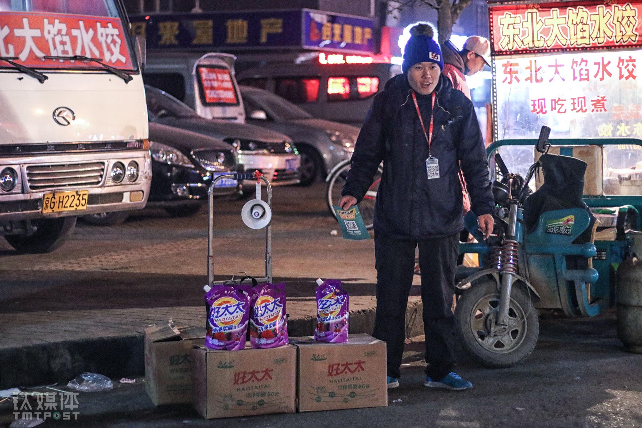 2015年11月18日,北京街头,闫军祥在做地推,他身旁摆放着地推礼品。彼时O2O大潮正逐渐退去,礼品比拼的背后,地推获取的用户,转化率连5%都达不到。晚上气温很低,闫军祥在下班的人潮中站了4个小时,挣了80块钱。(一名职业地推的自白)