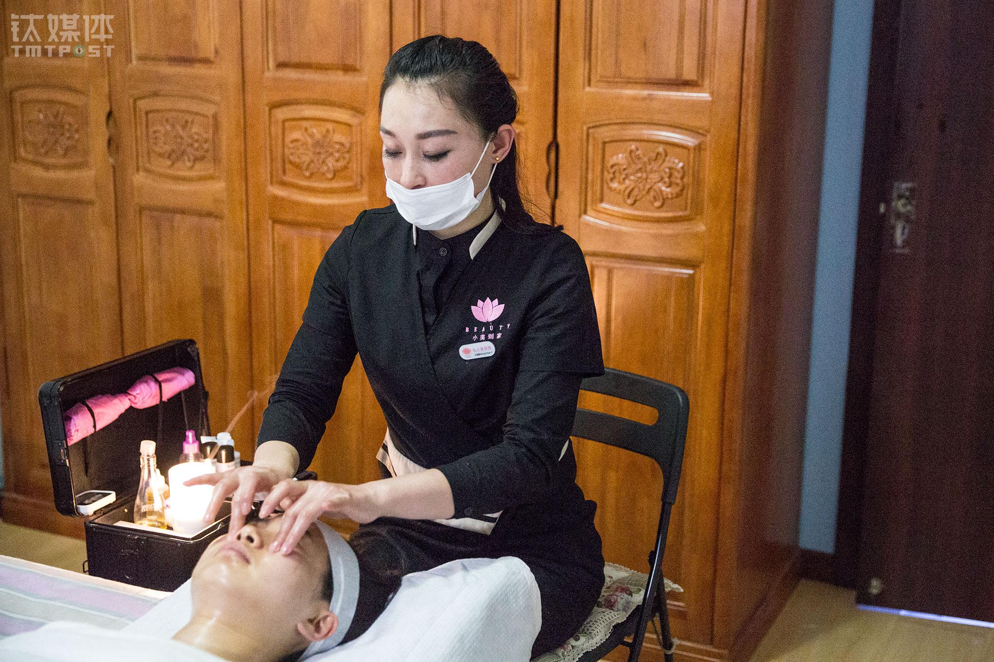 """2016年3月13日,O2O平台""""小美到家""""美容师王丽媛在客户家提供美容服务。她每天早上7点拖着30多斤的箱子出门,晚上10点回家,每天服务客户5~6名,常常忙到吃饭都顾不上。为了练习美容技能,她曾累到连筷子都拿不起。O2O上门服务,跟在美容店里提供服务相比,美容师和客户之间关系更平等、信任度更高。在钛媒体《在线》:《一个O2O上门美容师的一天,什么是劳动者的尊严》中,我们写道:劳动者的尊严来自物质,也来自人与人之间的彼此尊重,这种尊严,才是O2O带来的最大价值。"""