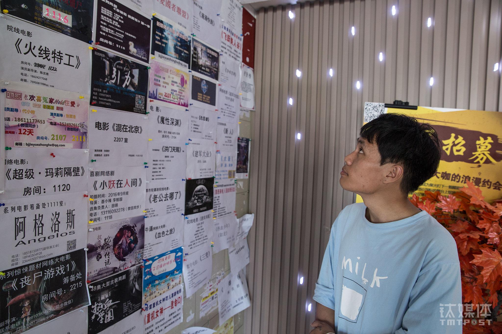 """2016年8月29日,北京大望路飘HOME酒店,李陆柒在剧组通告栏前寻找机会。这间酒店被称为""""网络大电影基地"""",剧组扎堆聚集,怀着演员梦的年轻人在这里来来往往。李陆柒一心想成为一名演员,他短时间地学过舞台剧,平时偶尔可以接到跑龙套和工作室小短片的活。(铁打的飘Home,流水的""""网络大电影"""")"""
