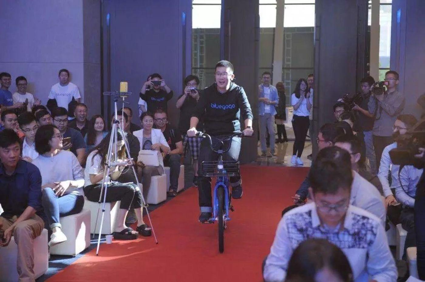 2016年11月的深圳发布会上,李刚骑车进入会场
