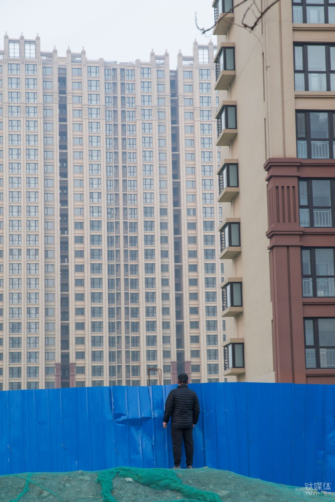 楼市观望者。北京通州,一名路人越过工地挡板望向一处住宅工地。