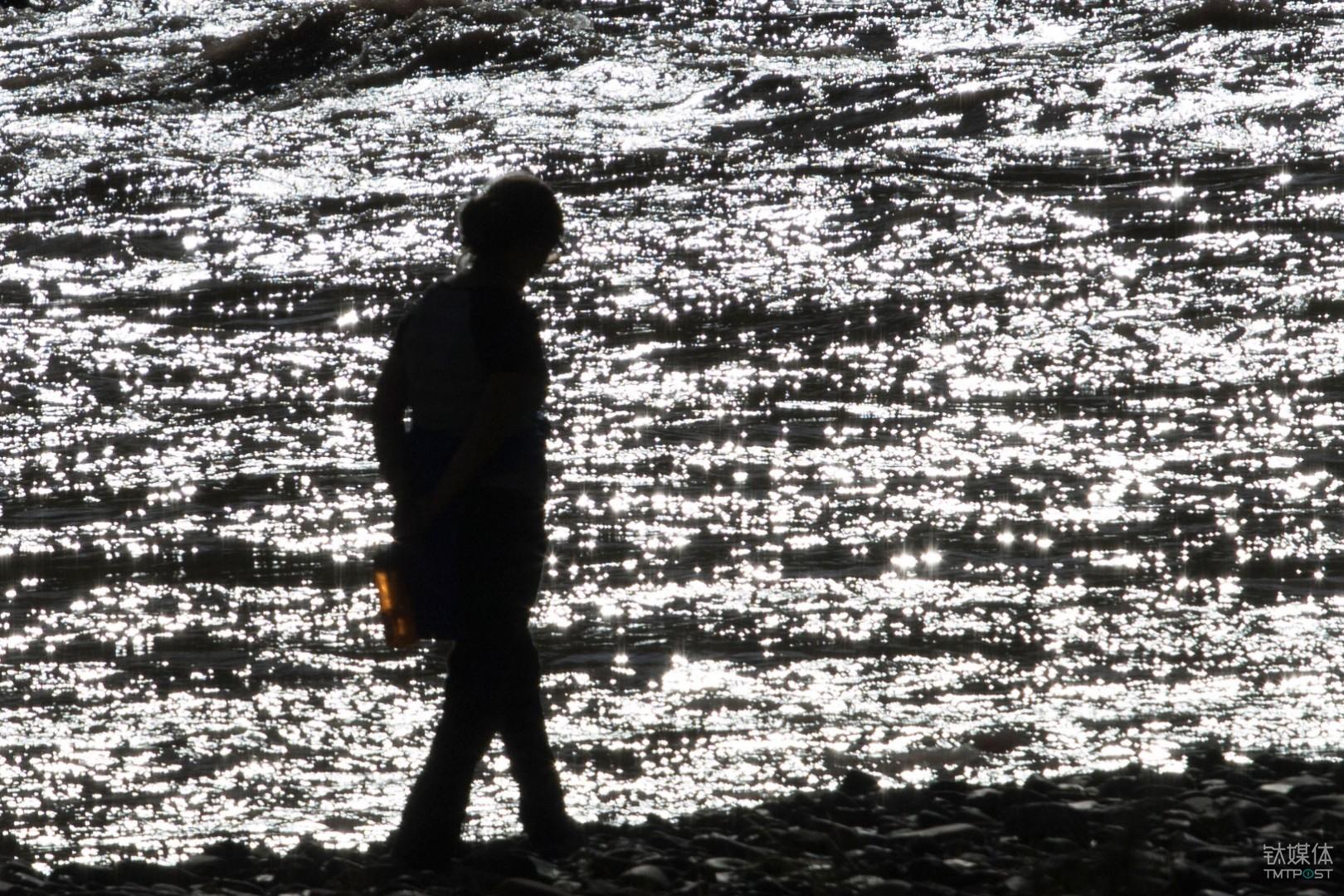 粼波微步。青海玉树杂多县,游客在澜沧江边散步。