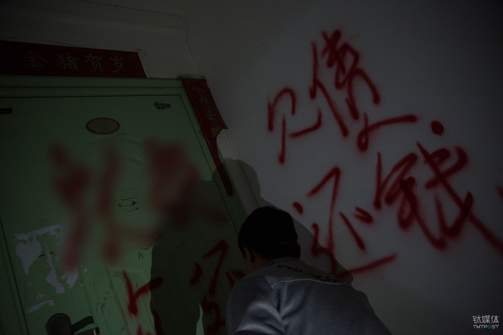 欠债还钱。广西,一名职业催债人在老赖家门上喷字。