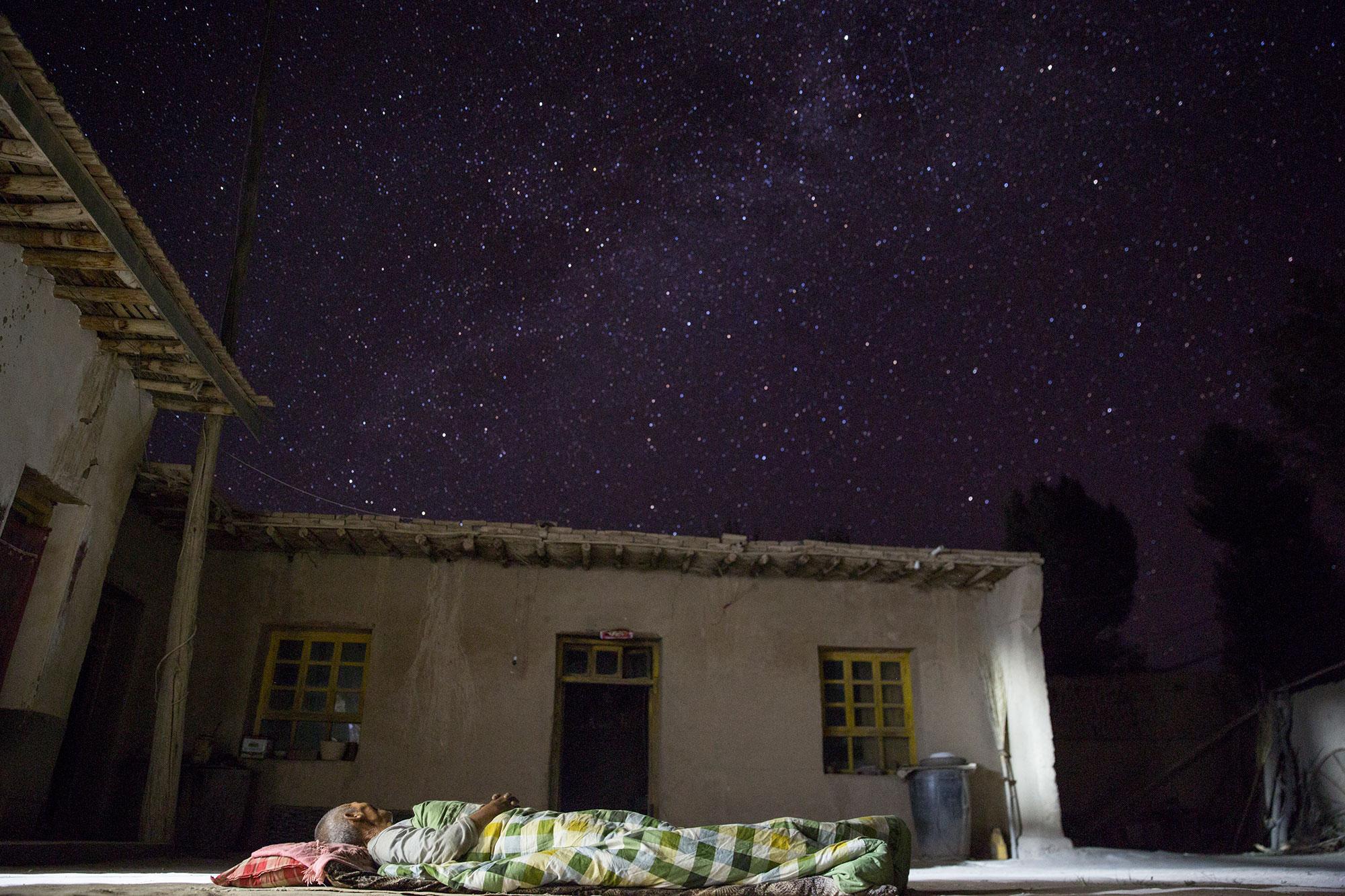 贫穷与富有。甘肃民勤,低保户李红善睡在自家简陋的院子里,仰面是浩瀚的星空。