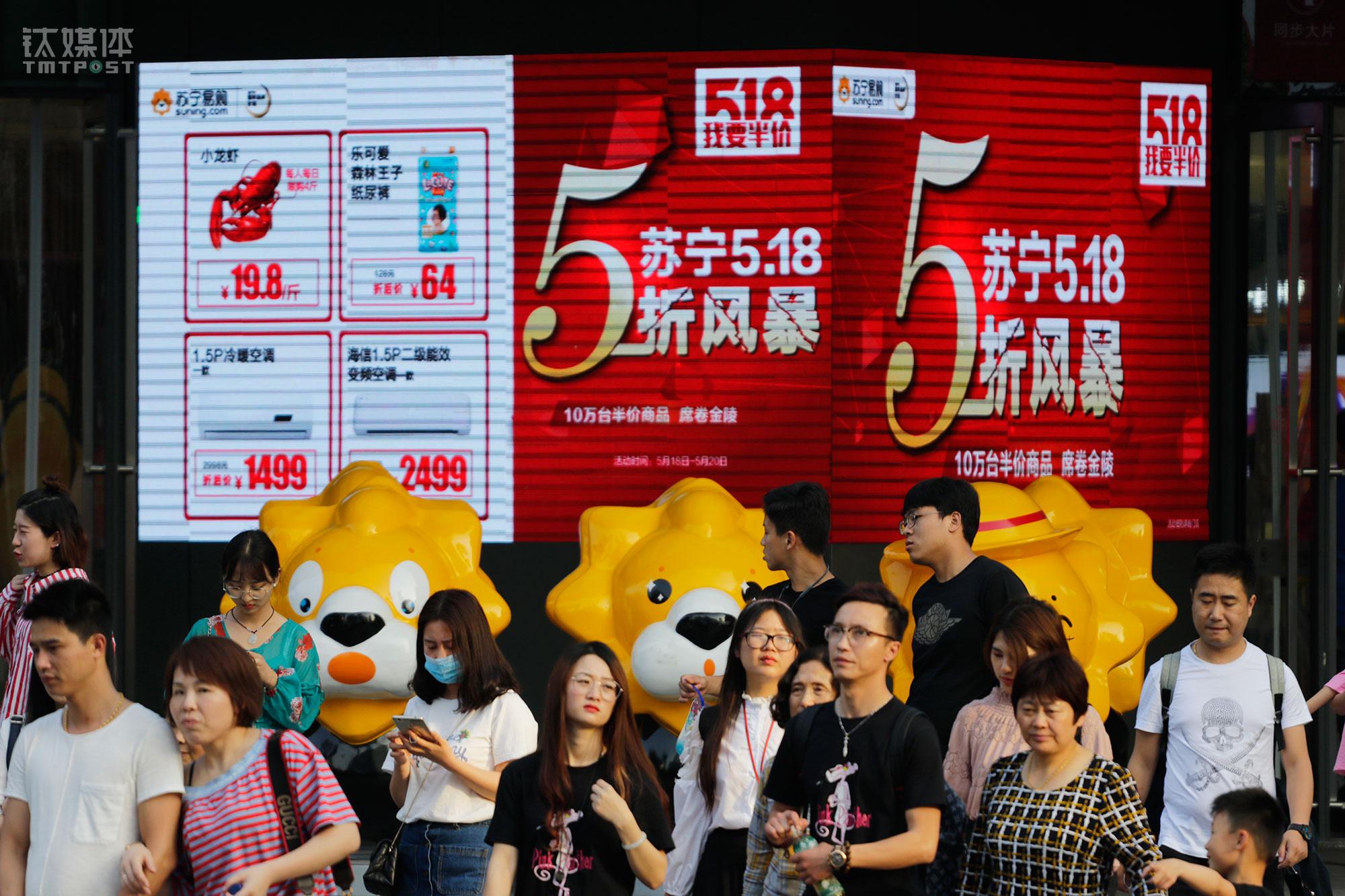 """5月13日,苏宁易购南京新街口店,屏幕上播放着""""5·18""""大促广告。这家店被苏宁成为云店3.0,里面设有家电卖场、家居馆、苏宁体育无人店、海鲜餐厅、苏宁影城、机器人咖啡店、苏宁极物等,是苏宁""""智慧零售""""的标杆店。"""