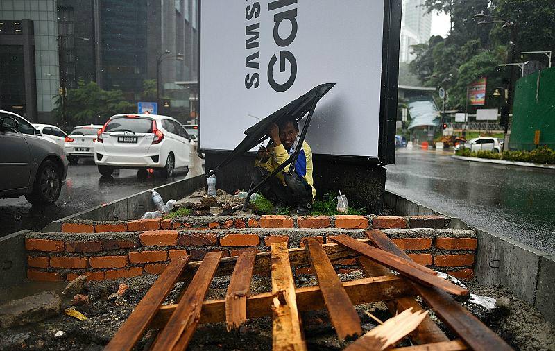2018年1月9日,马来西亚吉隆坡,一名工人在街边躲雨,图片来源:视觉中国