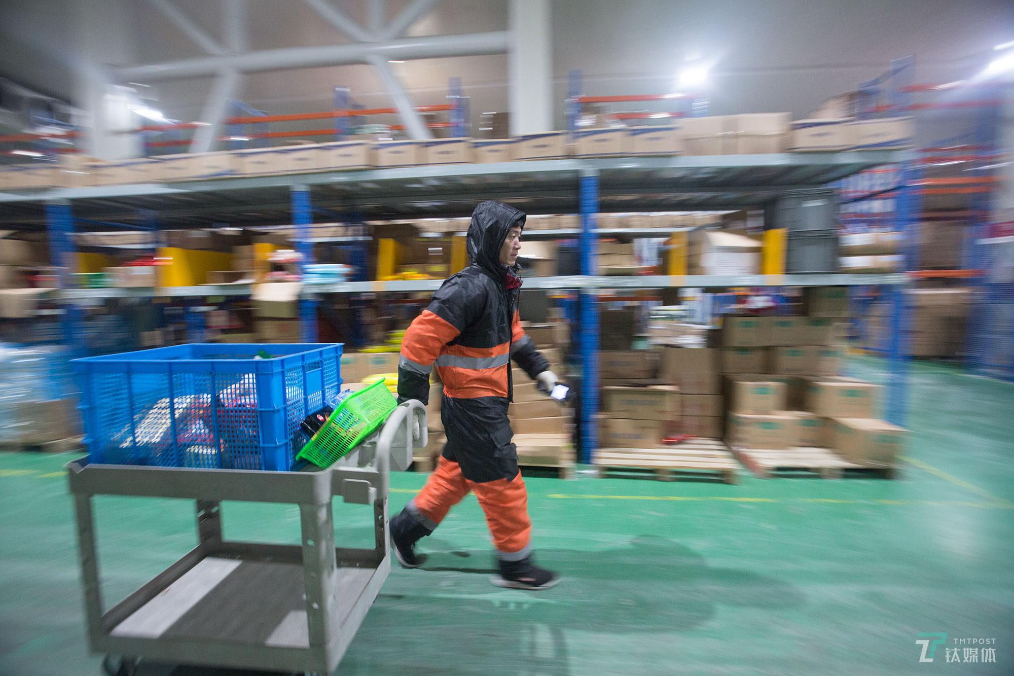 拣货员张修景拉着拣货车在货架之间穿梭。目前京东在全国有10多个生鲜冷库,生鲜冷链配送已覆盖全国300多个城市,冷链日均仓库订单处理能力100万件。张修景所在的这个冷库主要辐射华北地区。