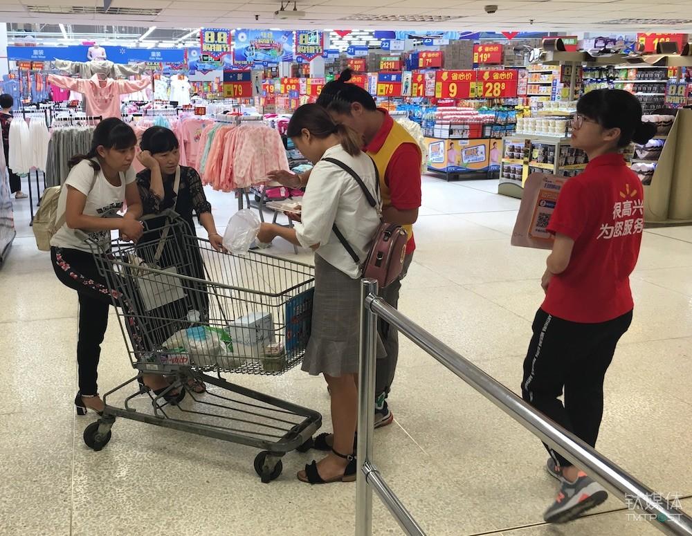 沃尔玛共工作人员正在指导消费者使用扫码购