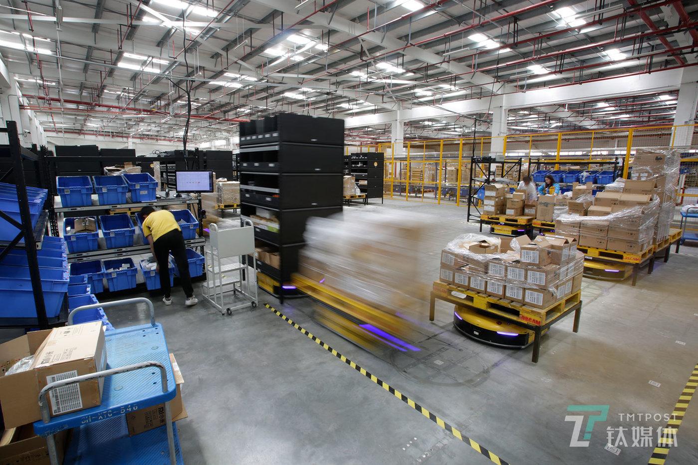 """【我和机器人同事】5月11日,上海,苏宁3C仓库,AGV物流机器人排队往拣货工作站运送货架。AGV物流机器人用""""货到人""""的方式改变了传统电商仓库""""人到货""""的拣选方式。"""