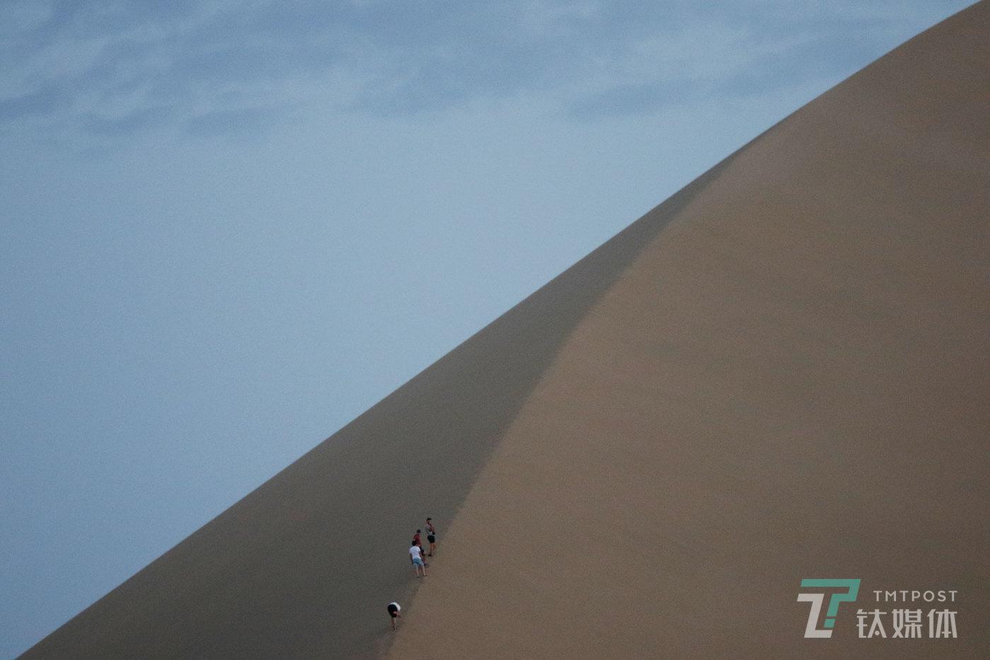【越过沙丘】8月19日,甘肃敦煌鸣沙山,攀爬沙山的游客。