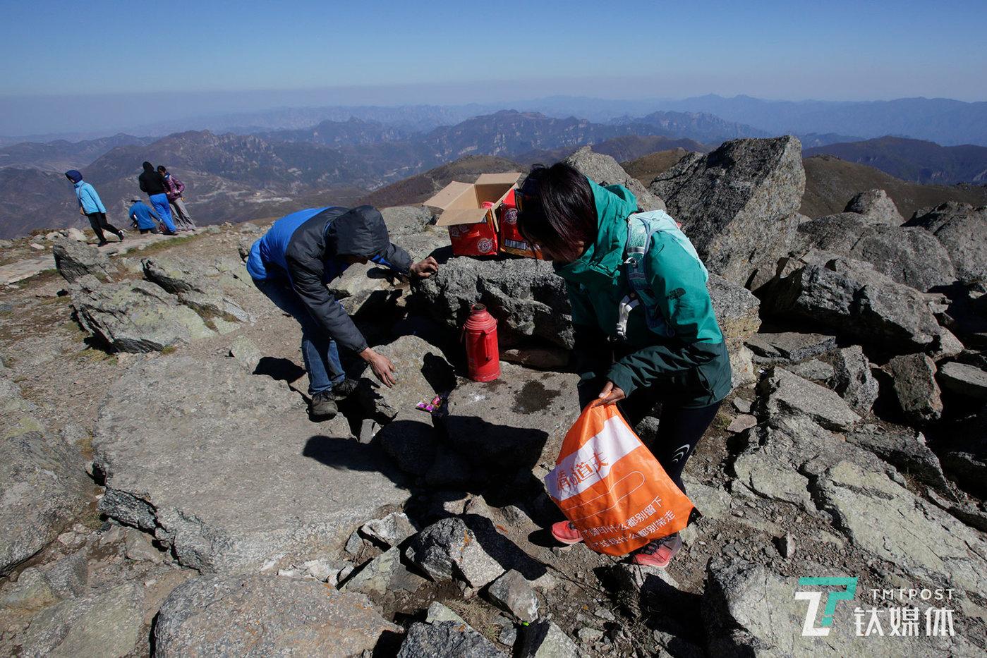 【山脉清道夫】10月2日,北京东灵山,海拔2303米的峰顶,山脉户外的驴友在自发捡拾游客留下的垃圾。