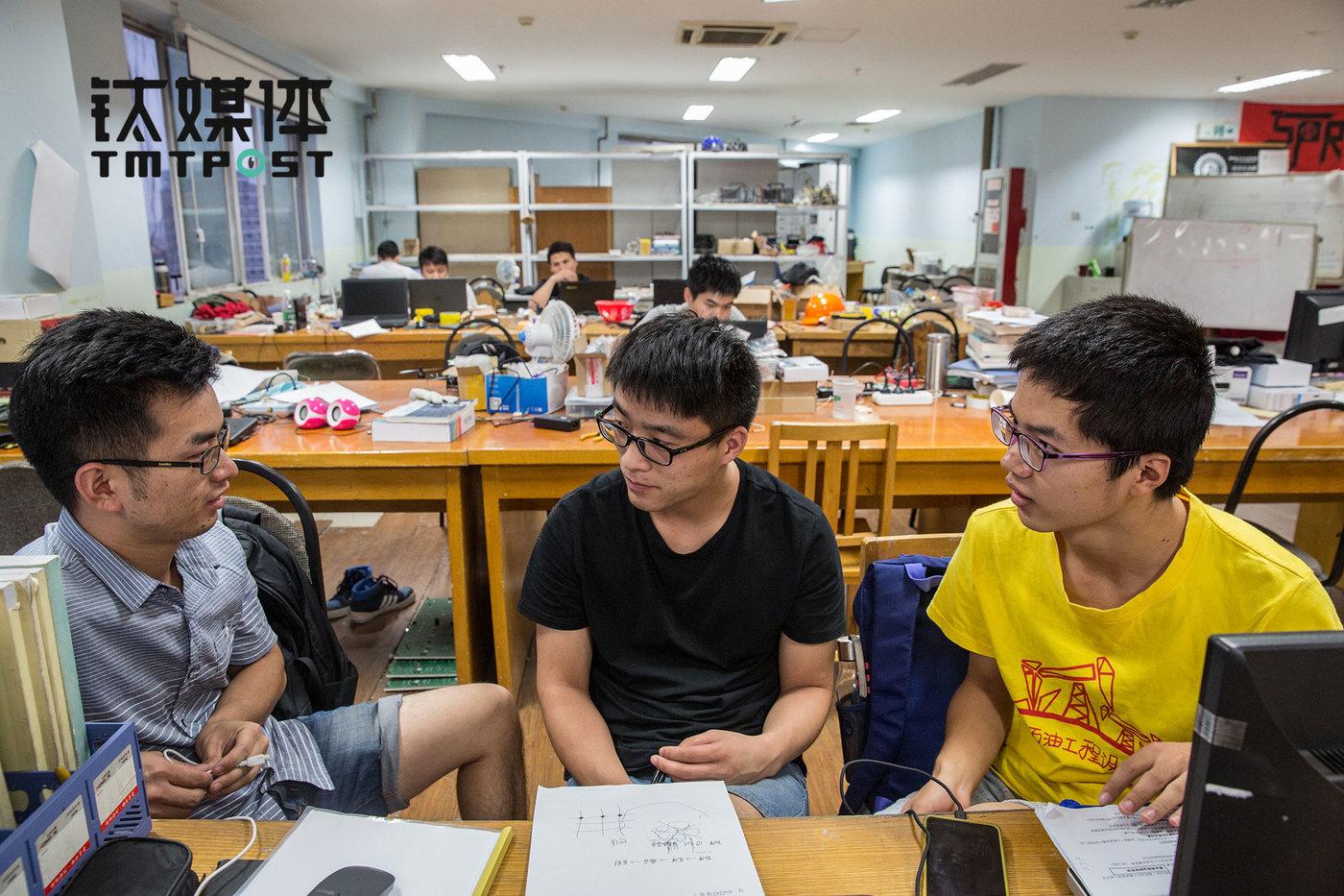 队员汪文松(中)和队友讨论新一届Robocon的规则,汪文松今年大四,目前正在找工作,他理想中的公司是大疆。而大疆作为Robomasters的赞助商,也将这一比赛作为发掘和培养人才的重要平台。